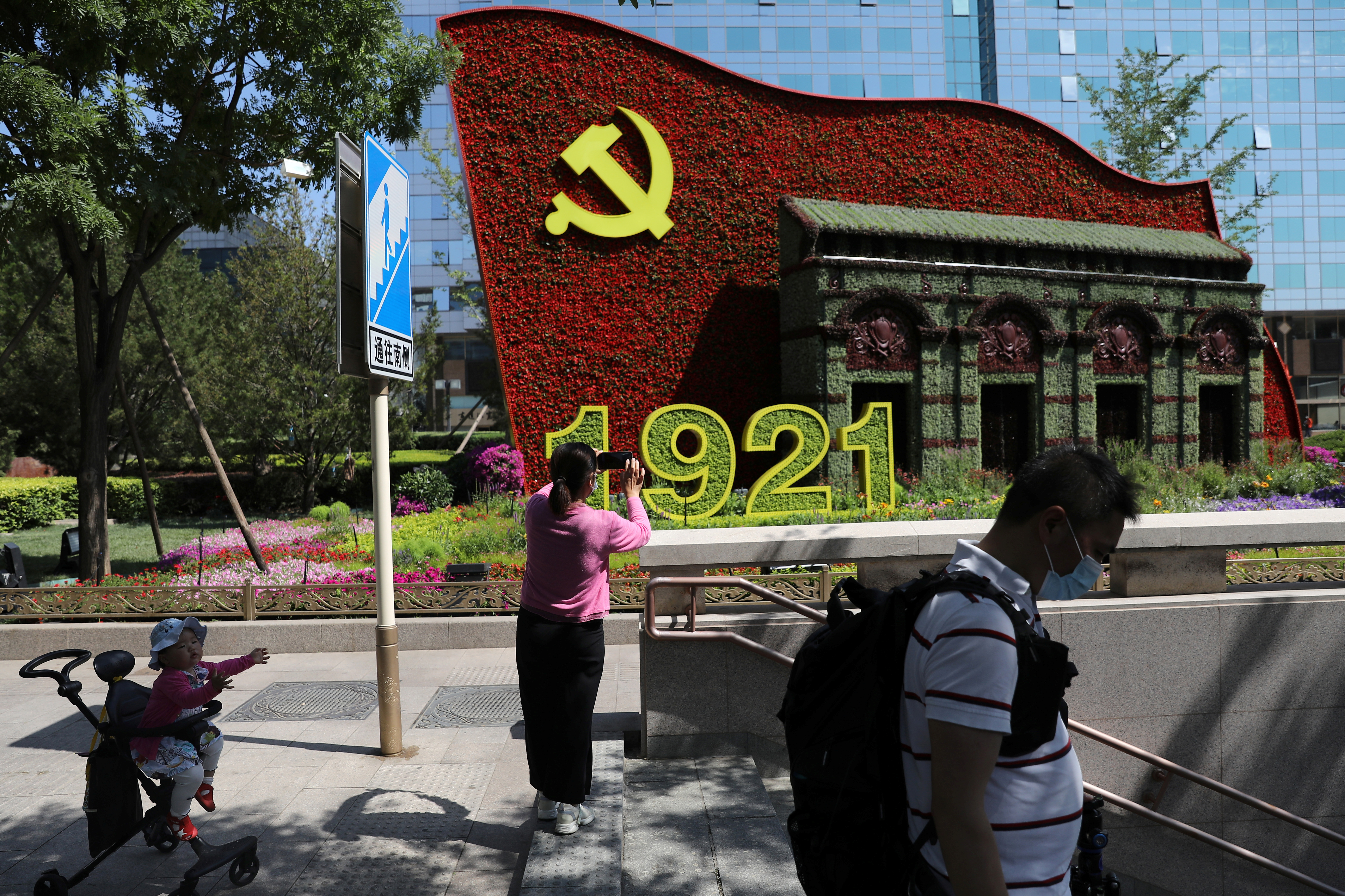 A woman uses her phone in front of a flower installation marking the 100th anniversary of the founding of the Chinese Communist Party of China, in Beijing, China June 21, 2021.  REUTERS/Tingshu Wang