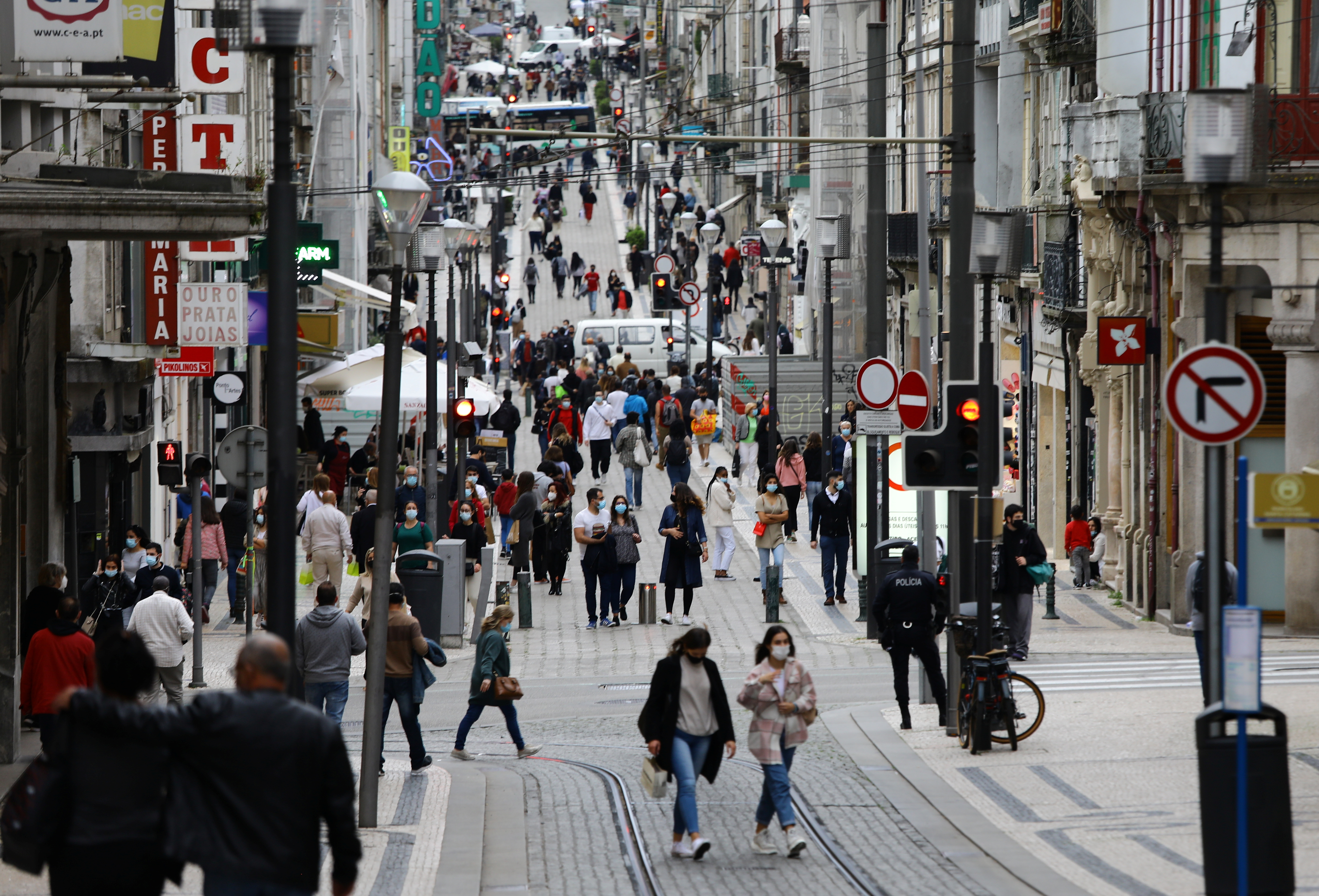 People walk in a street on the day when shops are allowed to reopen, amid the coronavirus disease (COVID-19) pandemic, in Porto, Portugal, April 19, 2021. REUTERS/Violeta Santos Moura