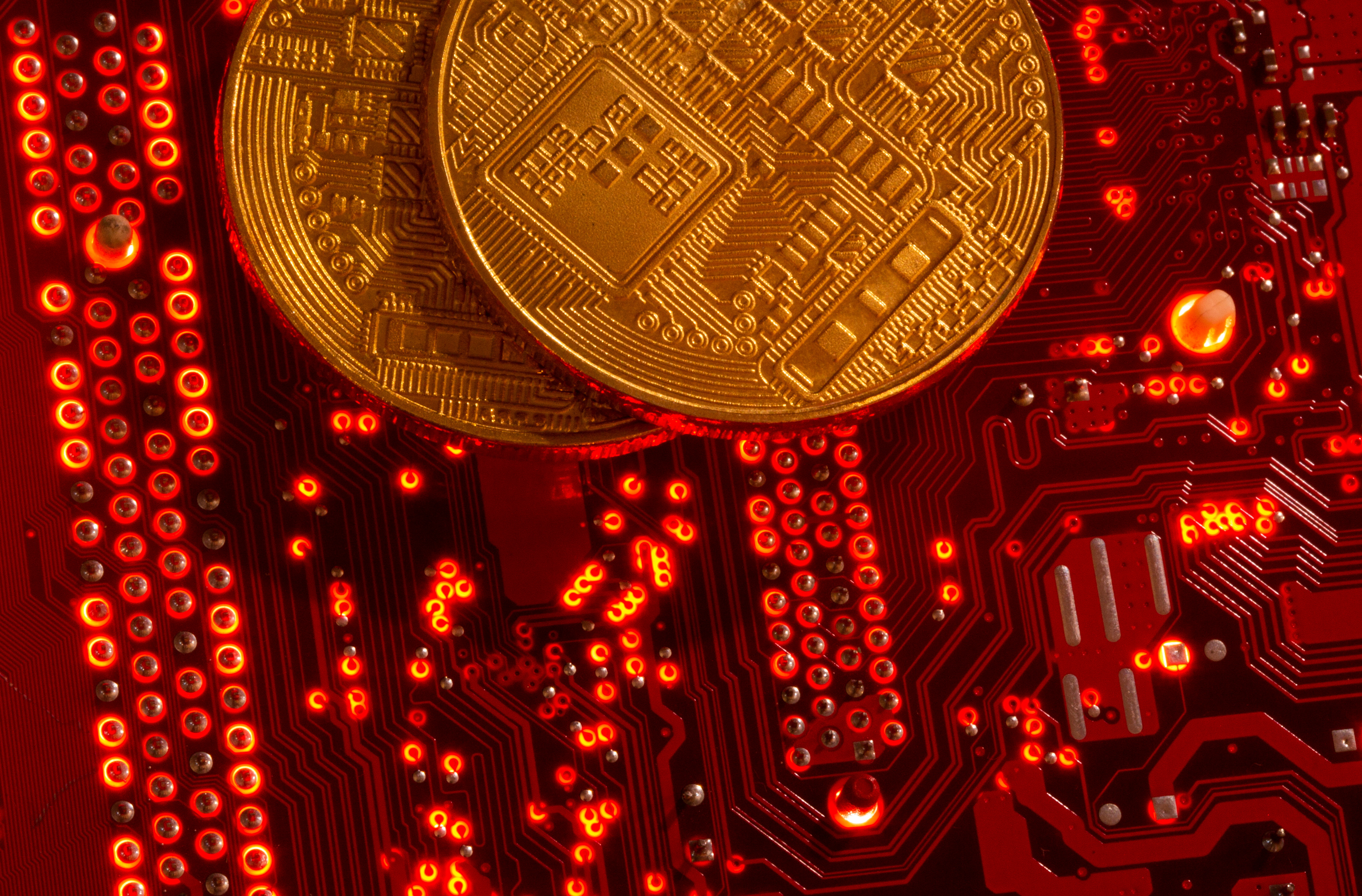 Representations of cryptocurrencies are placed on PC motherboard in this illustration taken, June 29, 2021. REUTERS/Dado Ruvic/Illustration
