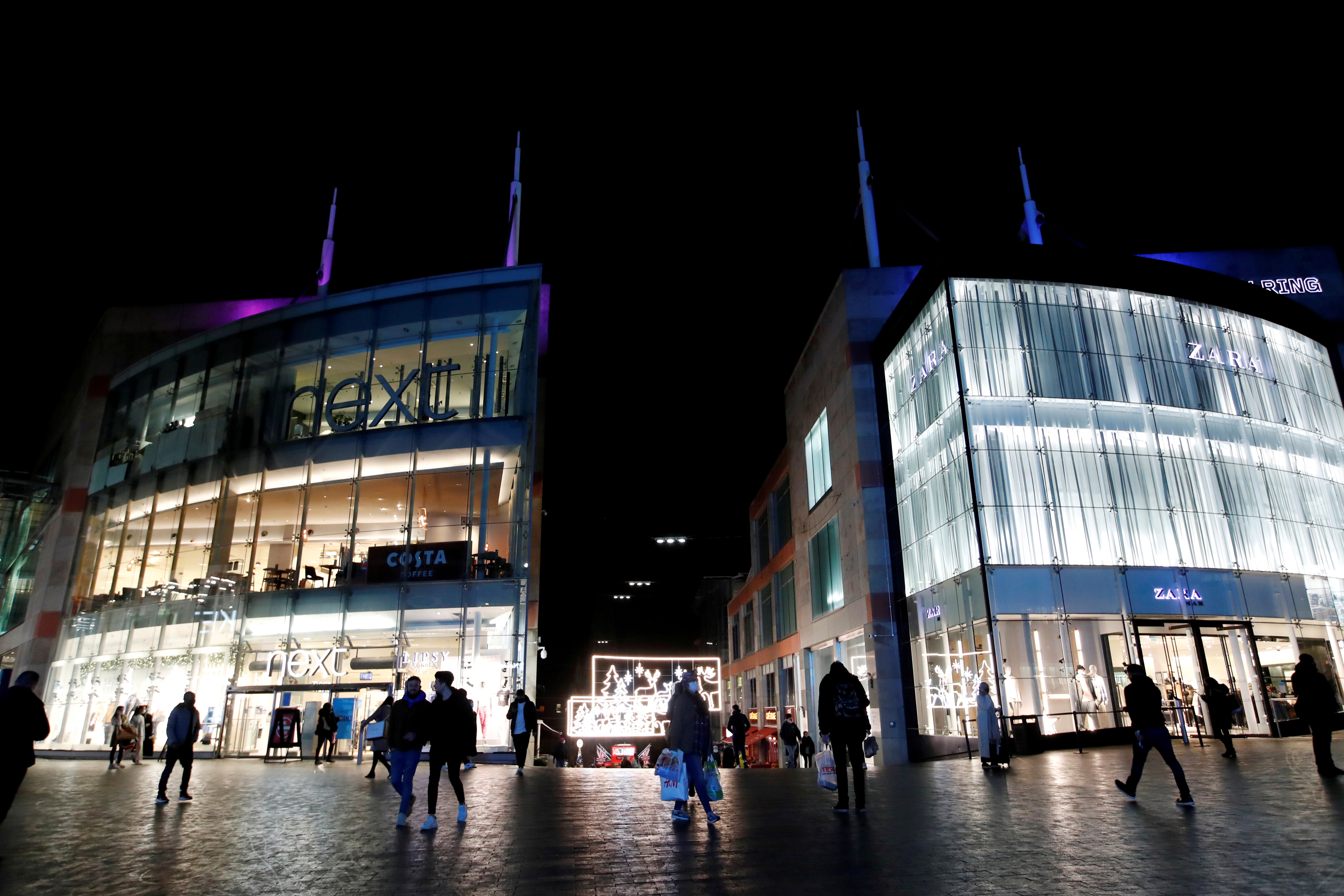 Shoppers are seen walking near Bullring shopping centre, owned by mall operator Hammerson, in Birmingham, Britain, November 4, 2020. REUTERS/Andrew Boyers