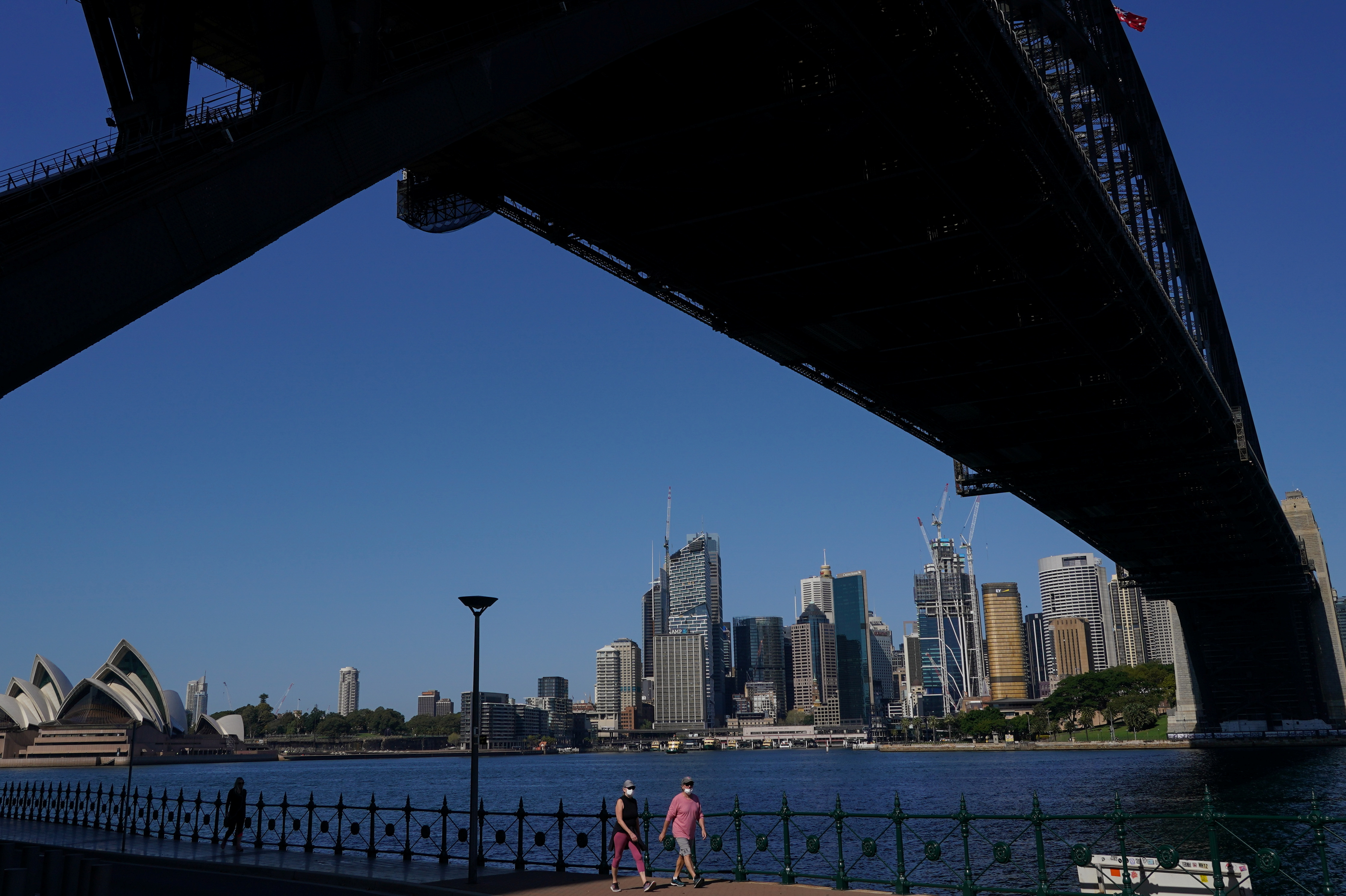 People in protective face masks walk under the Sydney Harbour Bridge during a lockdown to curb the spread of a coronavirus disease (COVID-19) outbreak in Sydney, Australia, September 3, 2021. REUTERS/Loren Elliott