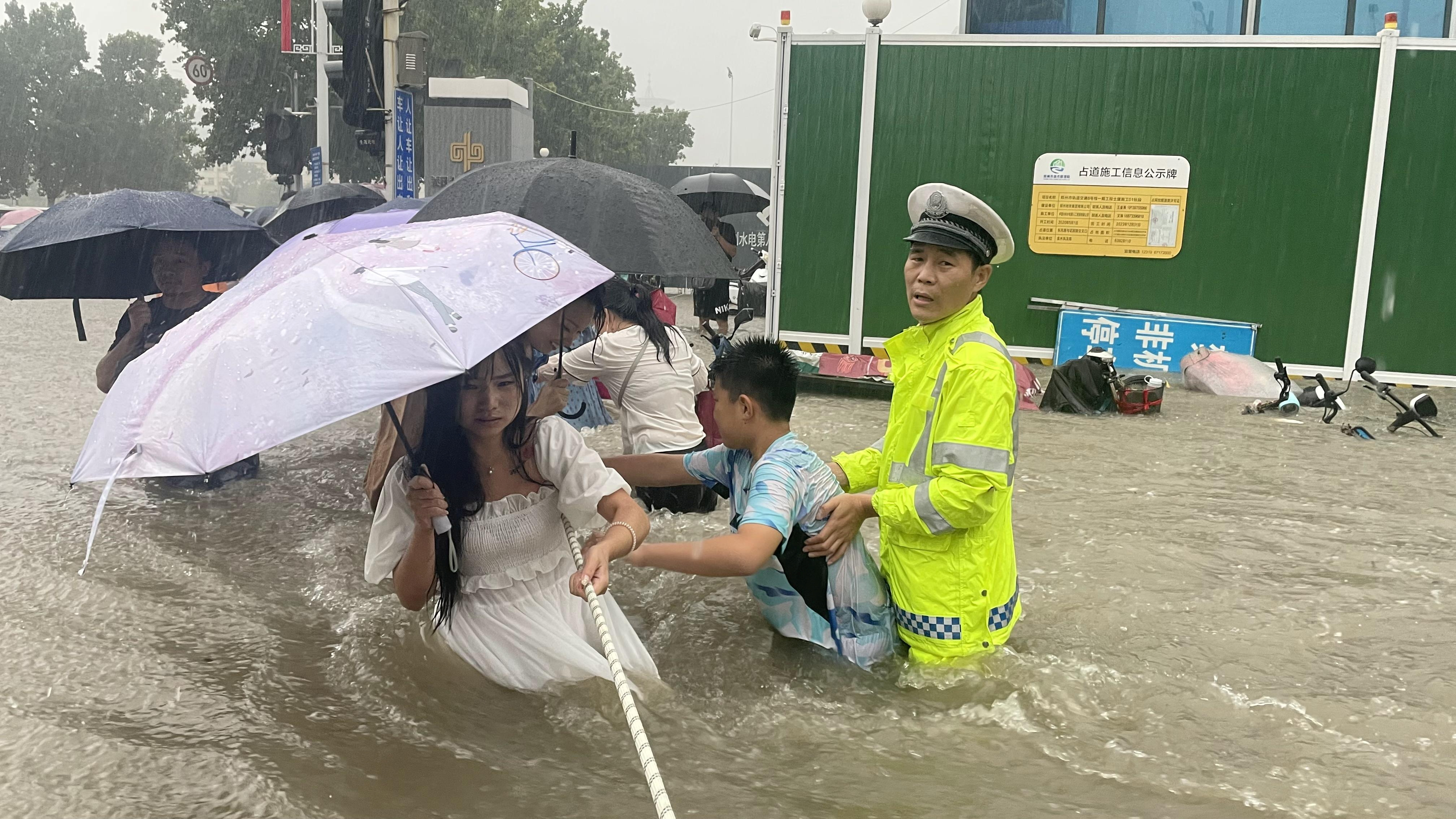 A traffic police officer guides residents to cross a flooded road with a rope during heavy rainfall in Zhengzhou, Henan province, China July 20, 2021. China Daily via REUTERS
