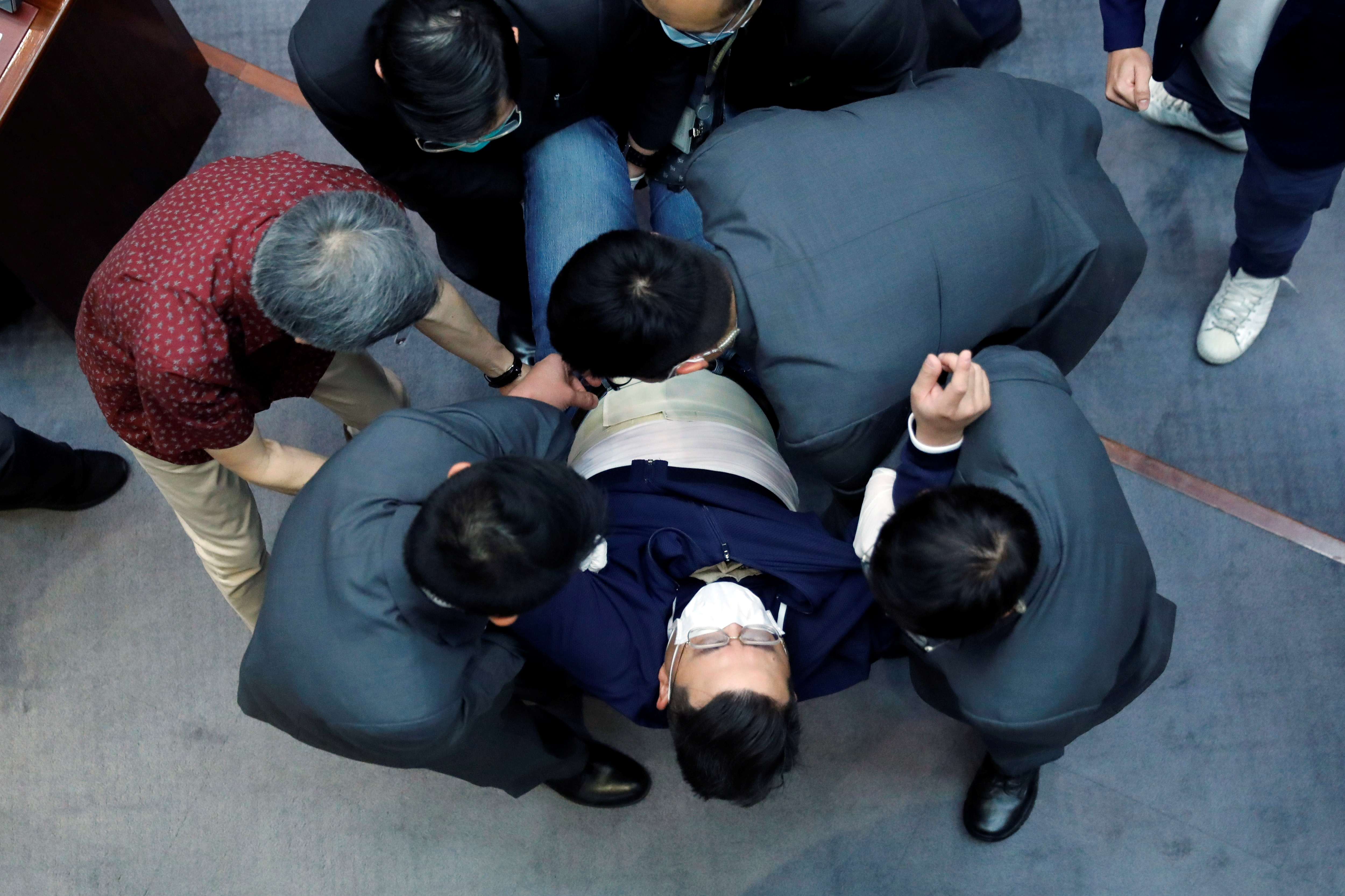 Pan-democratic legislator Andrew Wan is taken away by security as he protests against new security laws during the Legislative Council's House Committee meeting in Hong Kong, China May 22, 2020.  REUTERS/Stringer