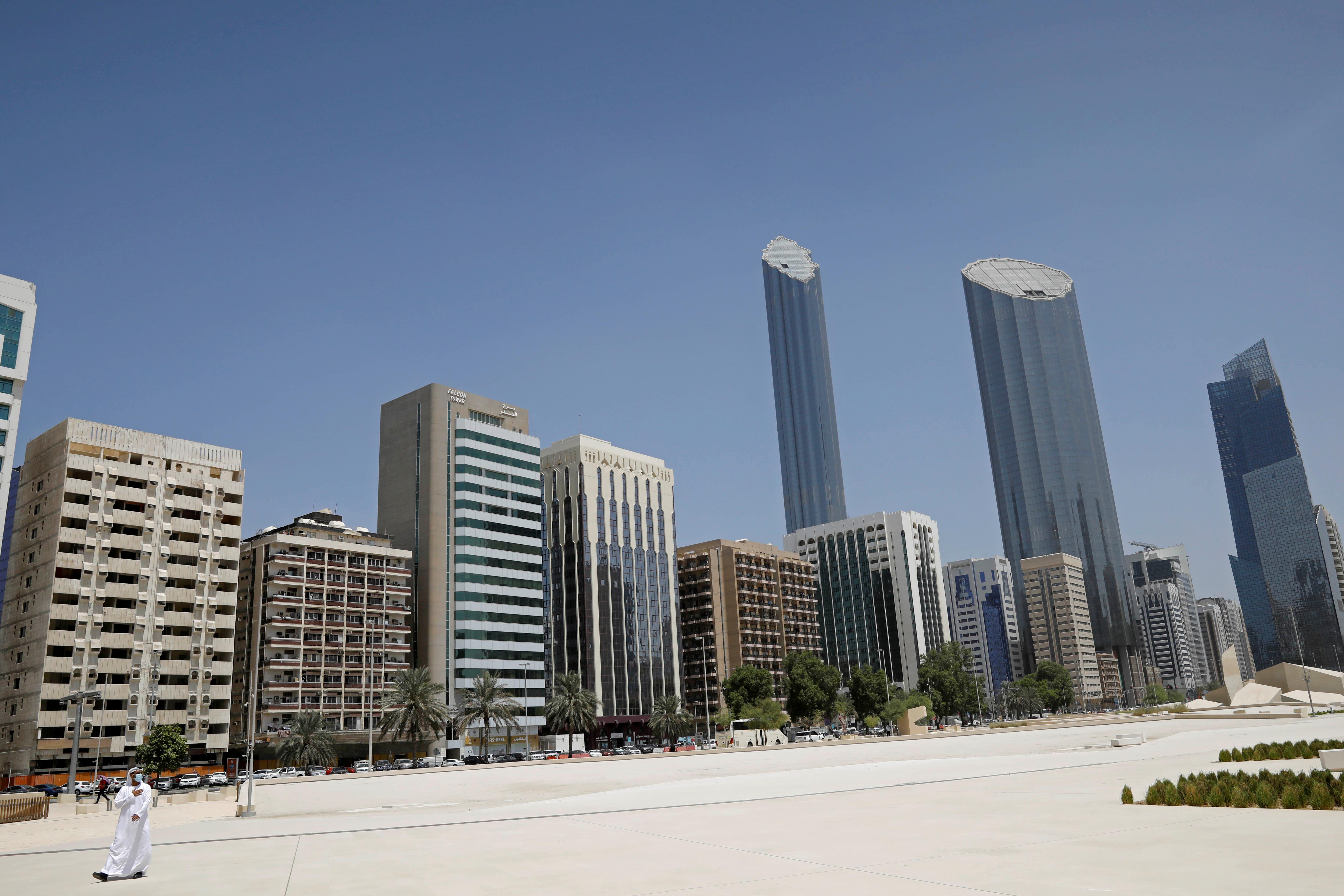 An Emirati man wears a protective mask as he walks past buildings in Abu Dhabi, United Arab Emirates September 1, 2020. REUTERS/Nir Elias/Pool/File Photo
