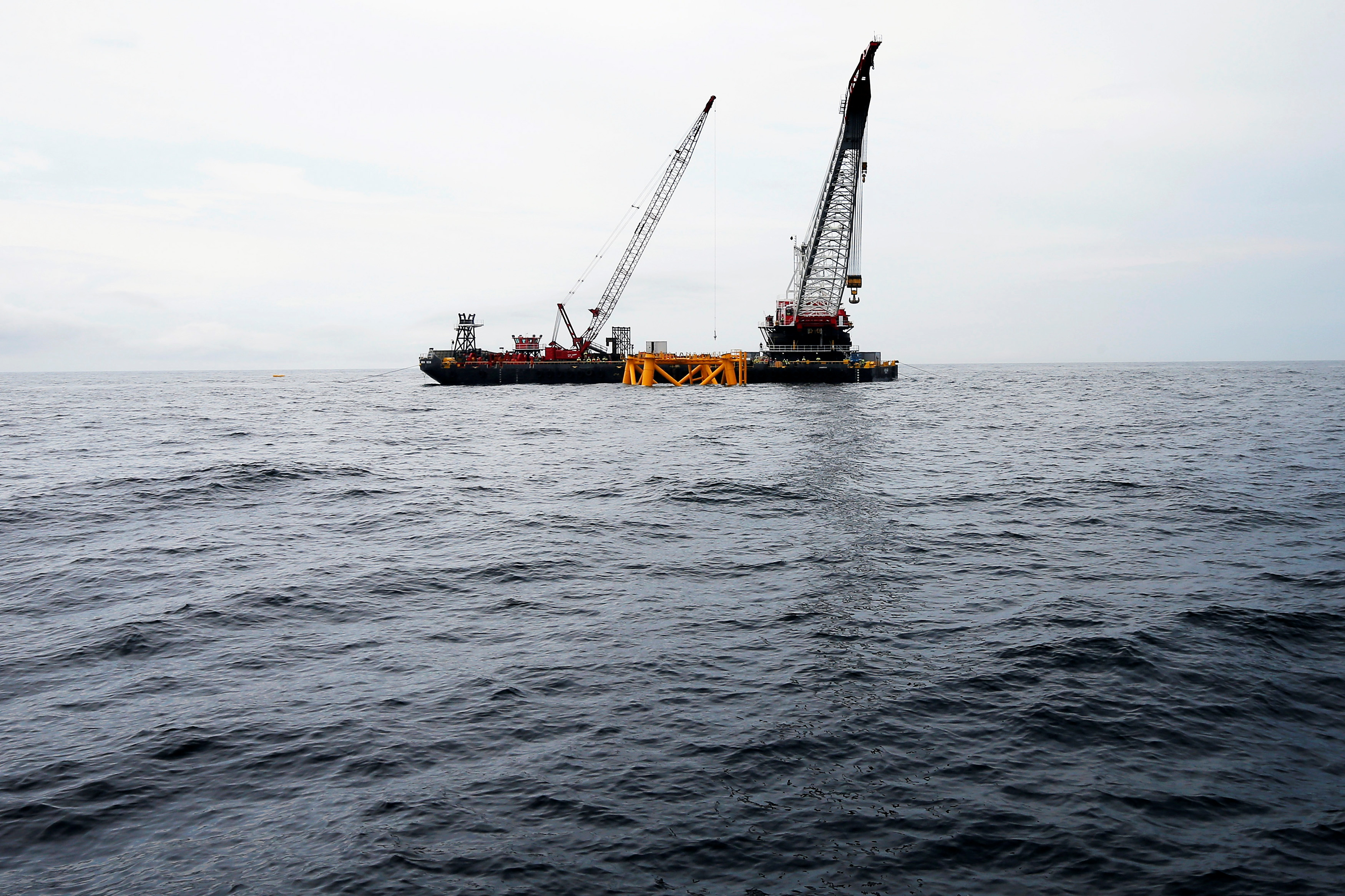 A crane hangs over the first jacket support structure installed to support a turbine for a wind farm in the waters of the Atlantic Ocean off Block Island, Rhode Island July 27, 2015. Deepwater Wind, a planned five-turbine, 30-megawatt wind farm off the coast of Block Island, would be North America's first offshore wind farm, a milestone the company says could pave the way for an industry long established in Europe but still struggling with opposition in the United States.        REUTERS/Brian Snyder/File Photo