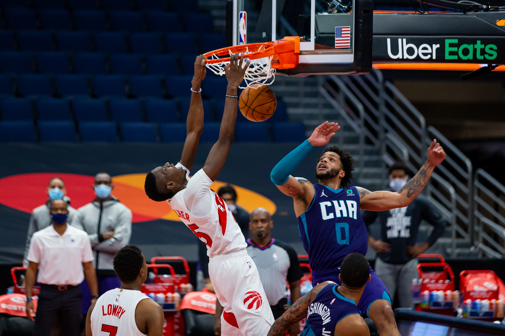 Jan 14, 2021; Tampa, Florida, USA; Toronto Raptors forward Chris Boucher (25) dunks over Charlotte Hornets forward Miles Bridges (0) during the fourth quarter of a game at Amalie Arena. Mandatory Credit: Mary Holt-USA TODAY Sports