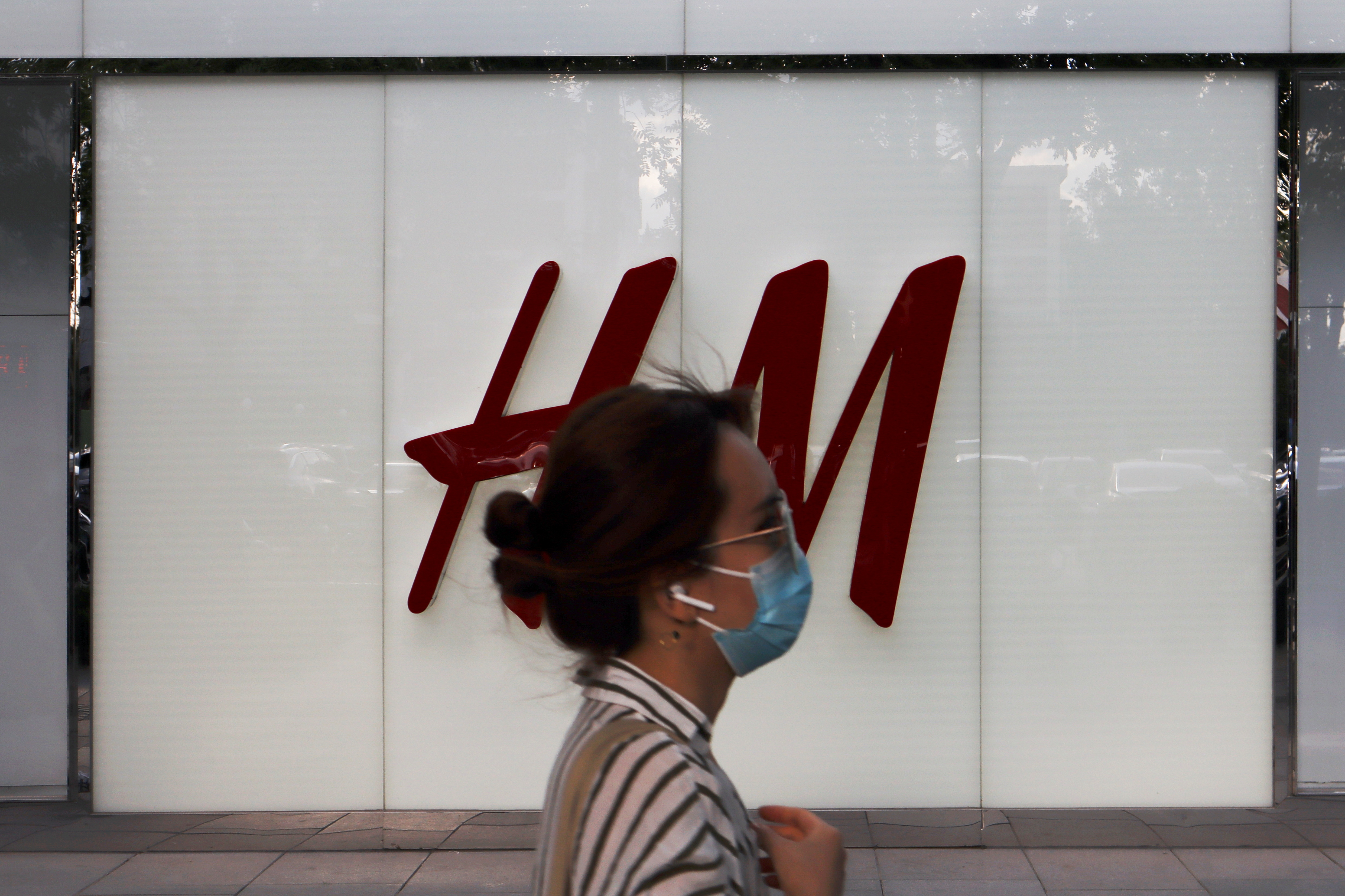 A woman walks past a store of the Swedish fashion retailer H&M at a shopping complex in Beijing, China May 24, 2020. Picture taken May 24, 2020. REUTERS/Florence Lo
