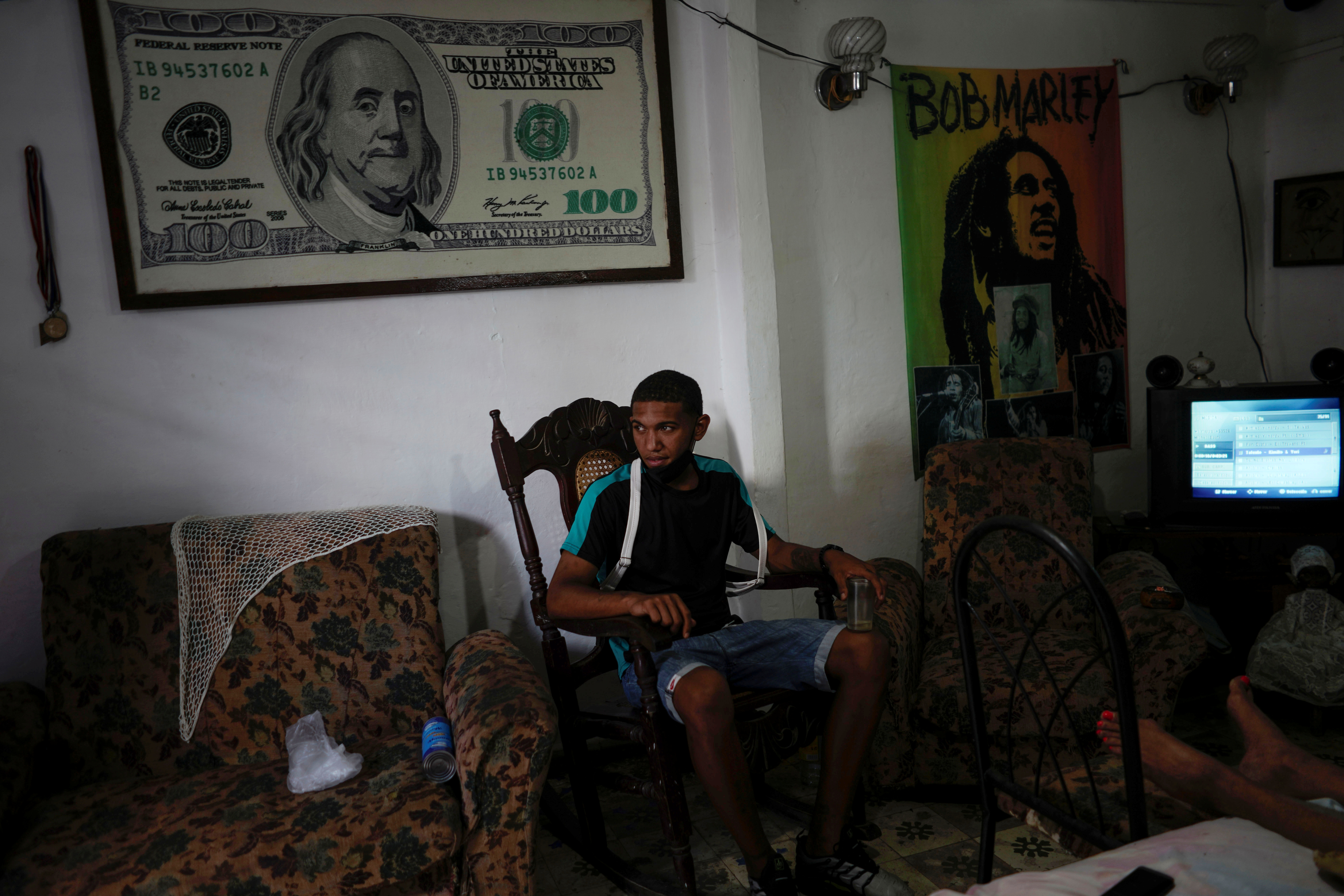 Student Alberto Martinez, 20, talks to relatives (not pictured) under an image with the design of a U.S. $100 bill in Havana, Cuba, March 17, 2021. Picture taken on March 17, 2021. REUTERS/Alexandre Meneghini