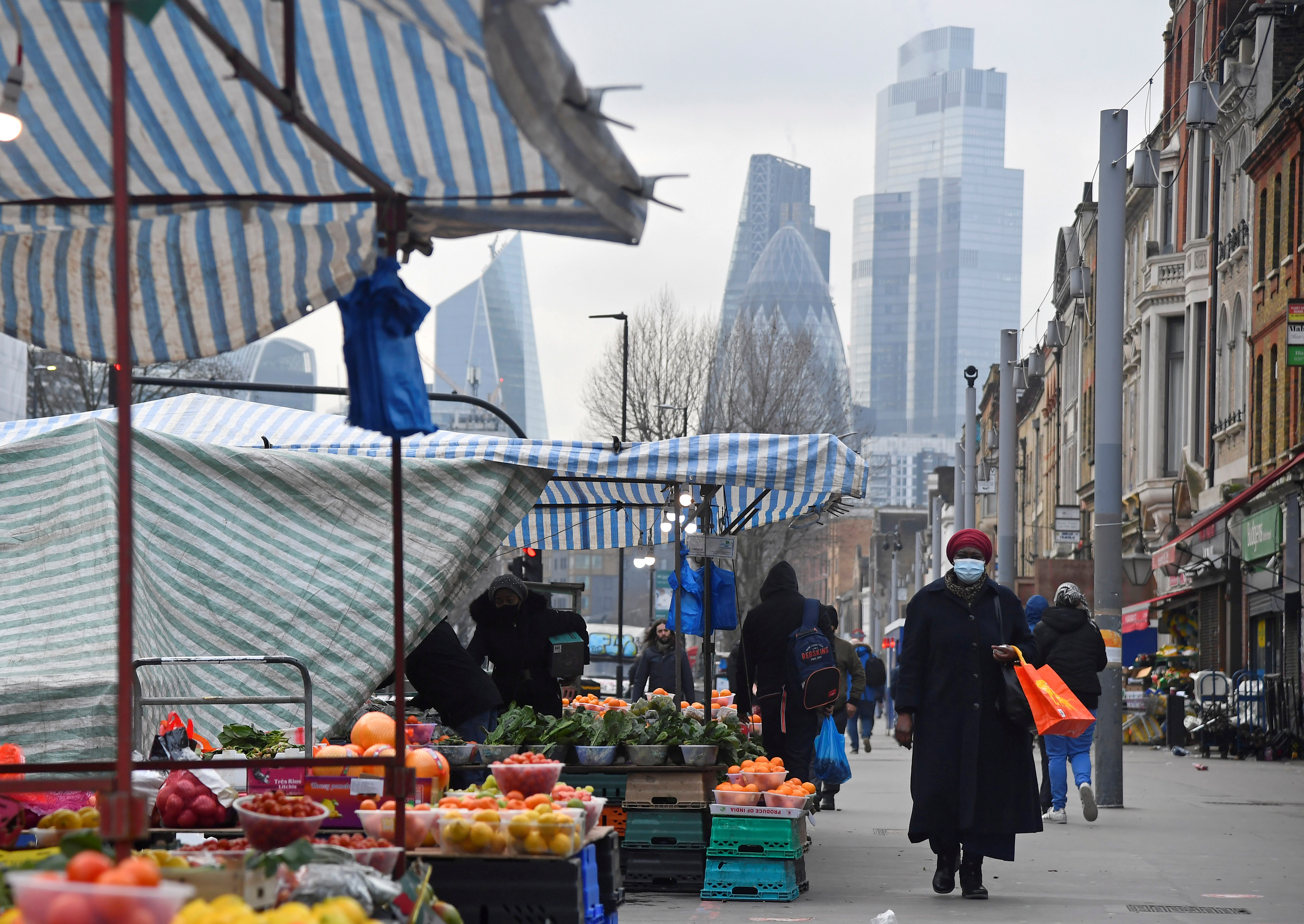 People shop at market stalls, with skyscrapers of the CIty of London financial district seen behind, in London, Britain, January 15, 2021. REUTERS/Toby Melville/File Photo