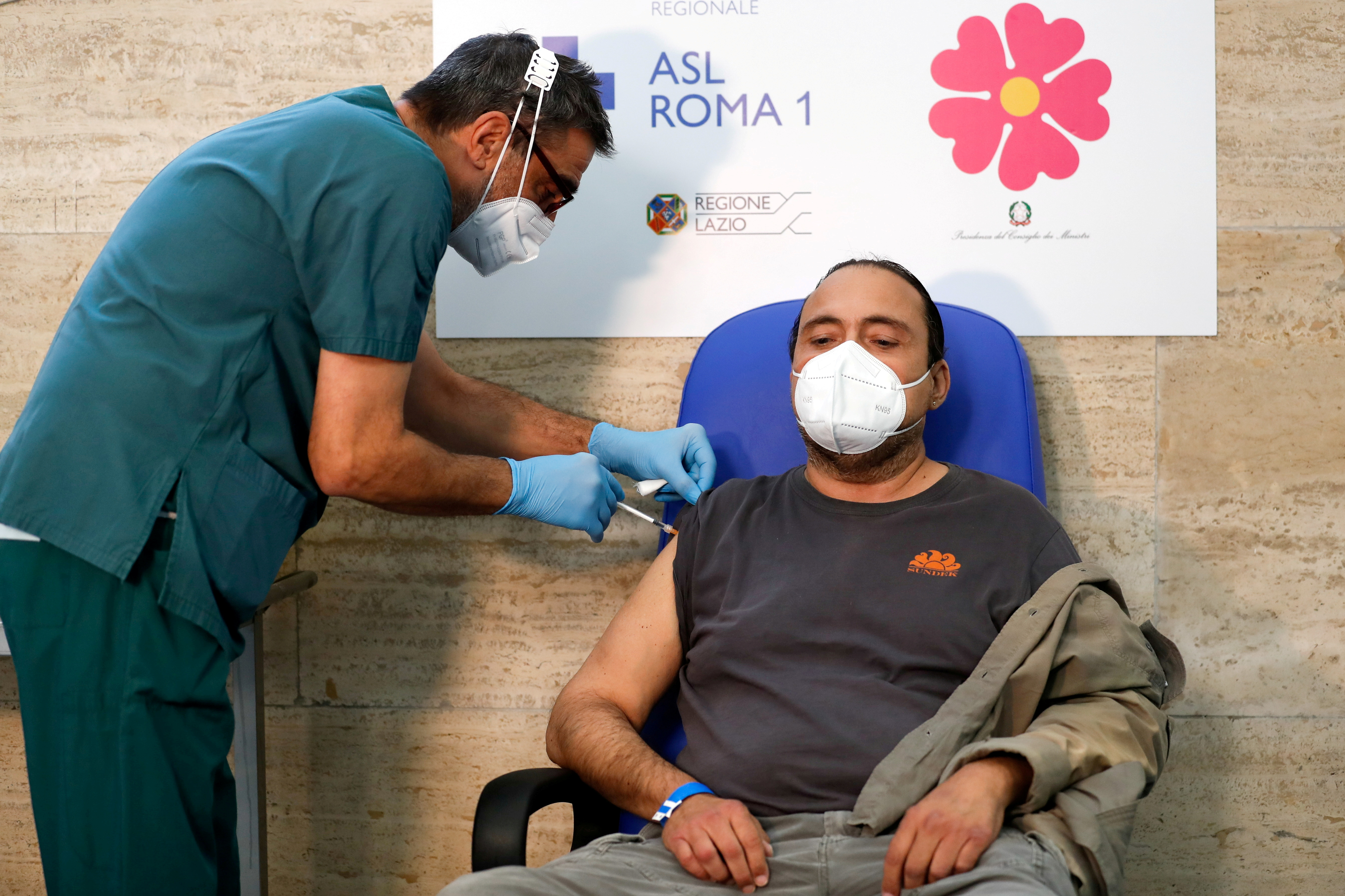 A health worker administers the third dose of a coronavirus disease (COVID-19) vaccine to Ivano Arcangeli, a patient deemed to be 'fragile', as vaccinations jump in Italy after the government made inoculation mandatory for all workers, in Rome, Italy, September 21, 2021. REUTERS/Yara Nardi/File Photo