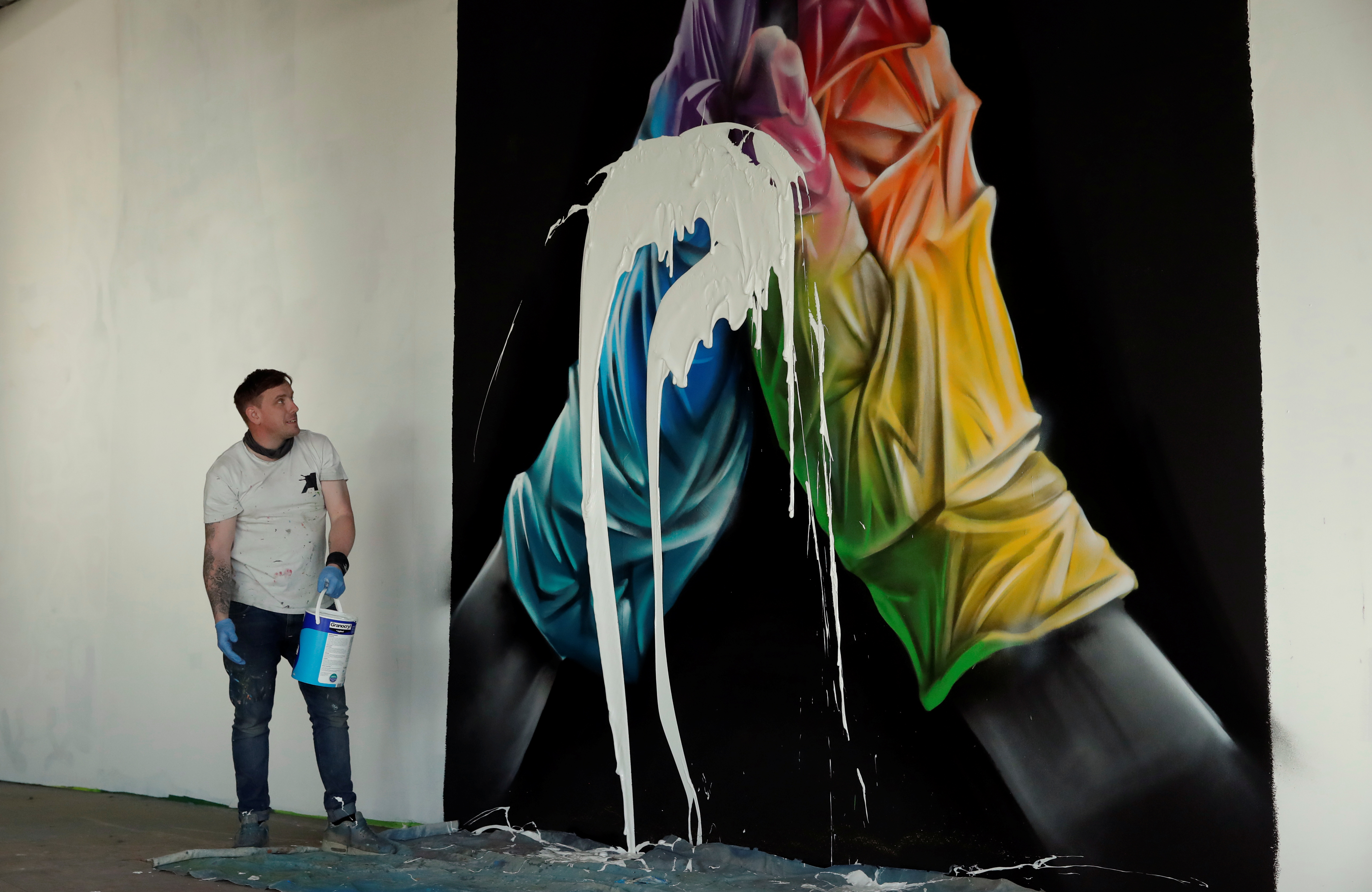 Street artist Nathan Murdoch looks at the artwork with paint splattered over it, as he creates a piece of crypto art to be auctioned with proceeds donated to the NHS in Peterborough, Britain, April 15, 2021. REUTERS/Andrew Couldridge