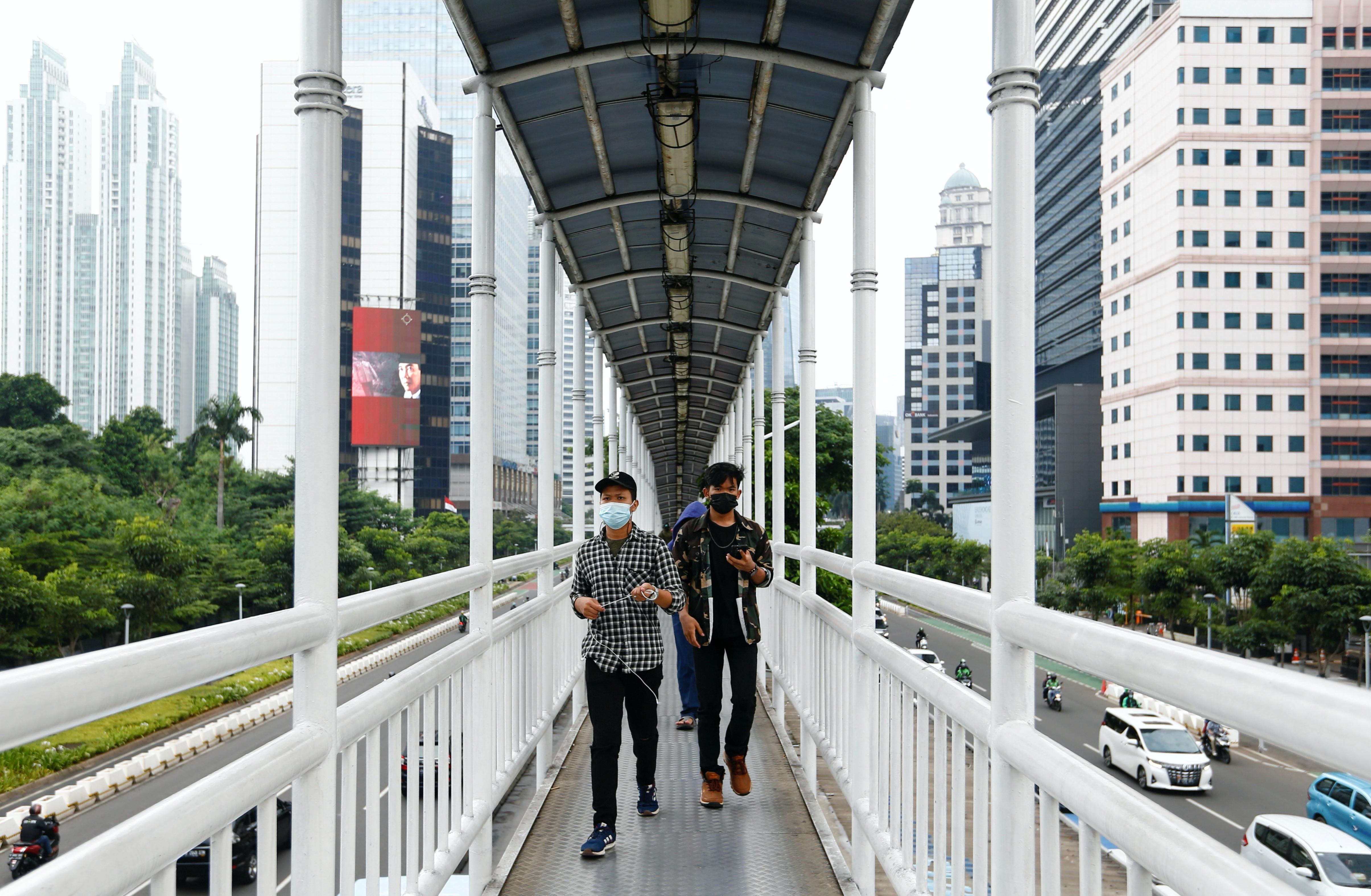 People wearing protective face masks walk on a bridge, amid the coronavirus disease (COVID-19) pandemic, in Jakarta, Indonesia, June 17, 2021. REUTERS/Ajeng Dinar Ulfiana