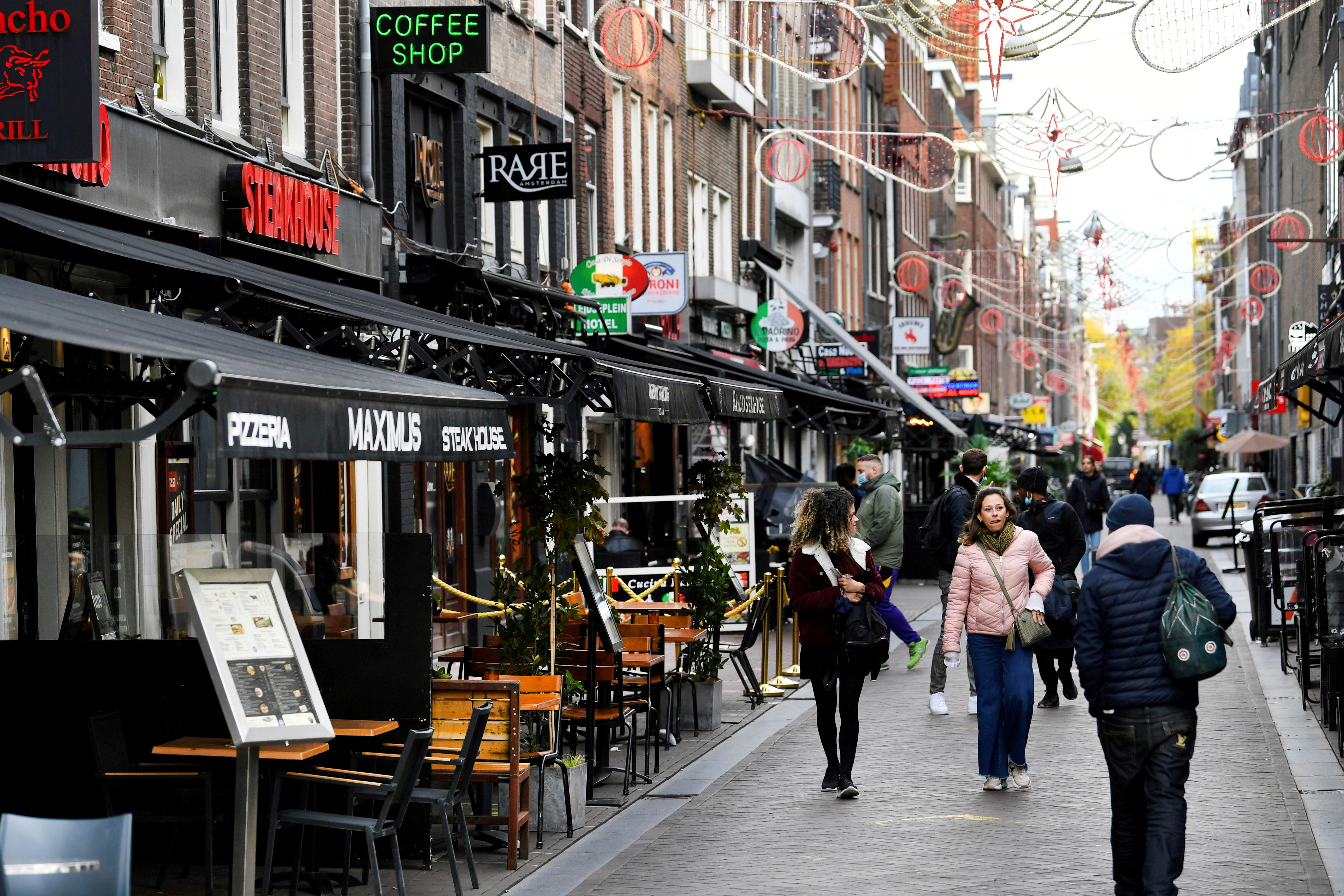 People walk past restaurants and bars as the Netherlands battles to control the spread of the coronavirus disease (COVID-19), in Amsterdam, Netherlands October 14 2020. REUTERS/Piroschka van de Wouw