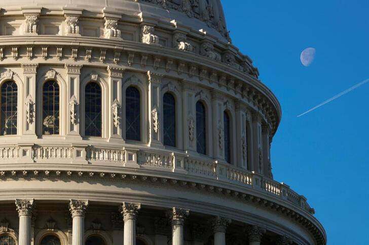 A plane flies across the sky beside the U.S. Capitol dome in Washington, U.S., January 15, 2020. REUTERS/Tom Brenner