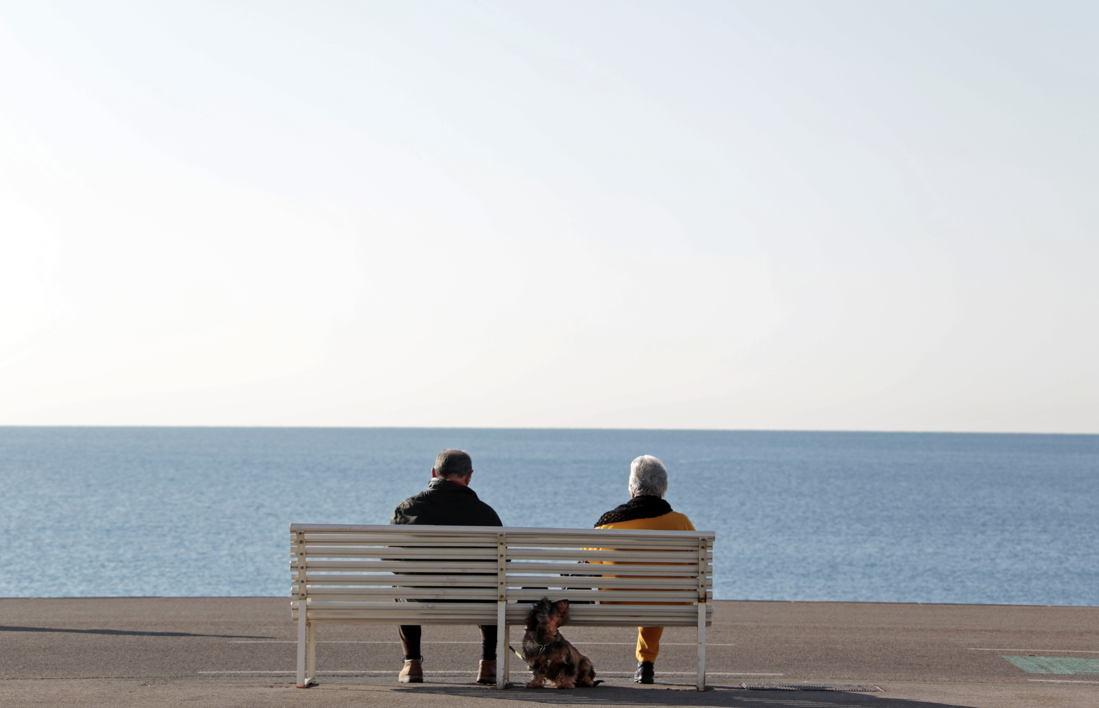 Elderly people sit on a bench to take in the sun with their dog along the Promenade Des Anglais in Nice February 19, 2013. REUTERS/Eric Gaillard