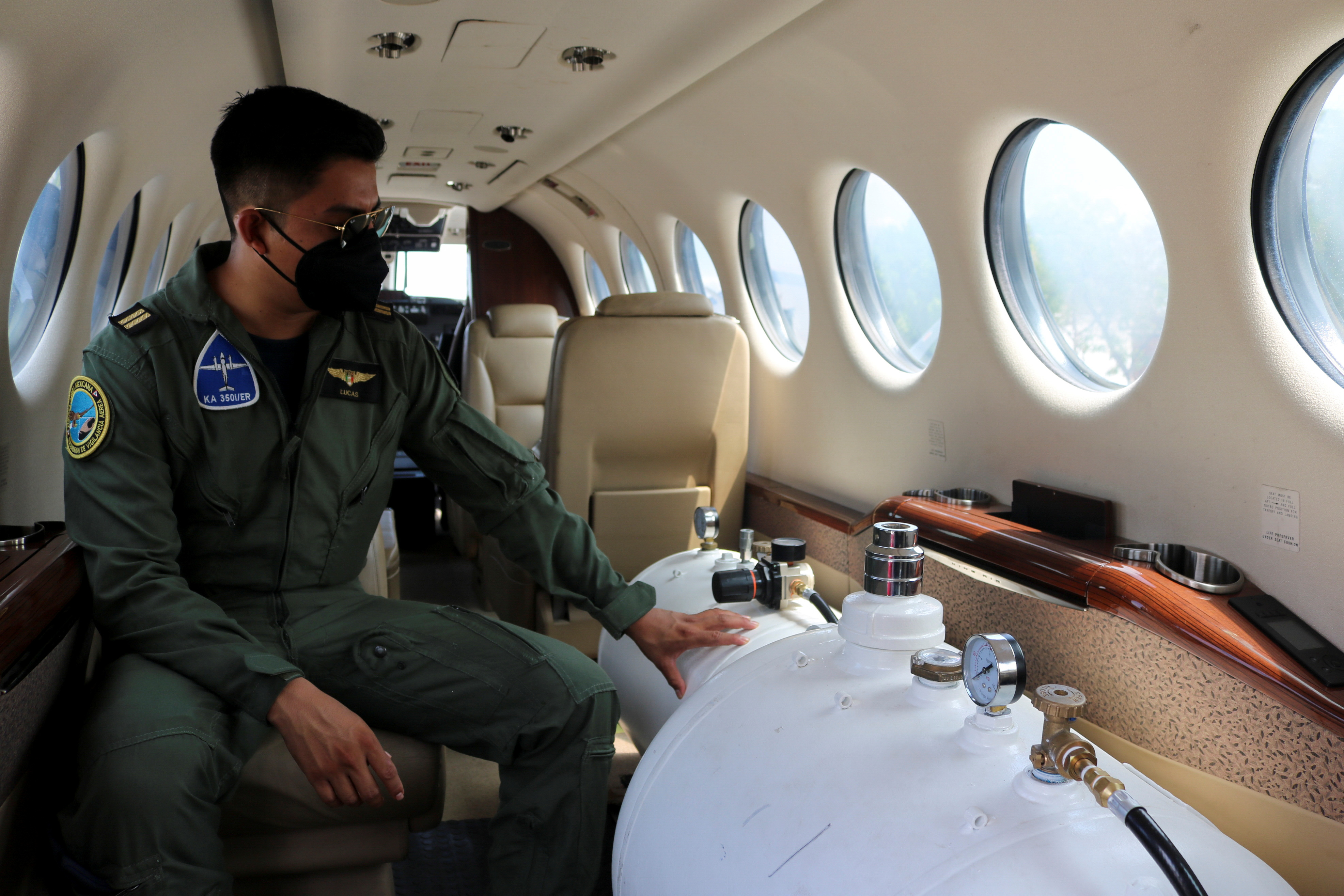 A member of the Air Force sit next to the tanks with cloud seeding solution in a King Air 350i plane, used for cloud seeding to enhance precipitation as part of the efforts to combat a long-term drought has hit two-thirds of Mexico, at the Military Air Base No. 10 in Culiacan, in Sinaloa state, Mexico June 25, 2021. REUTERS/Jesus Bustamante