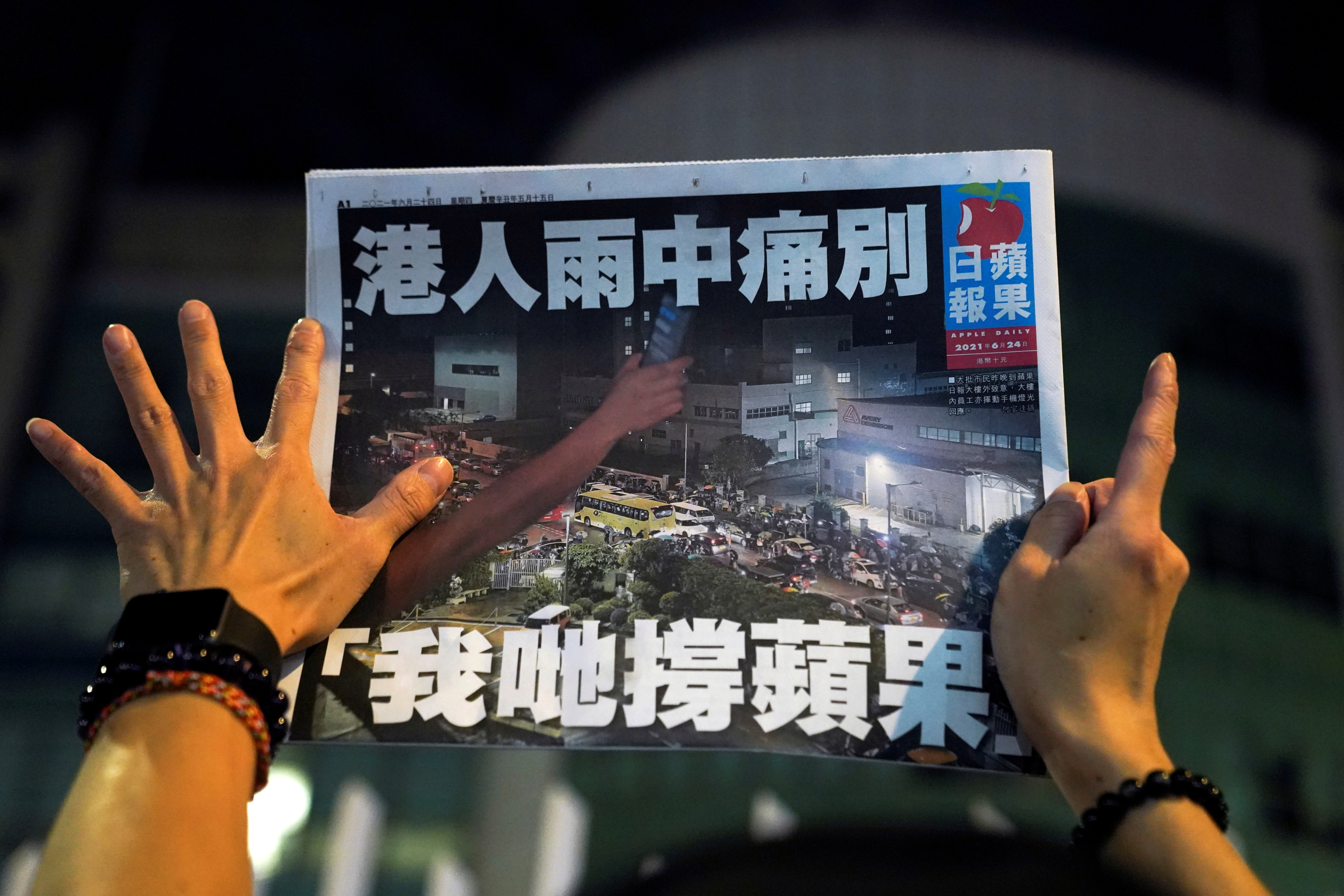 A supporter gestures while holding the final edition of Apple Daily in Hong Kong, China June 24, 2021. REUTERS/Lam Yik