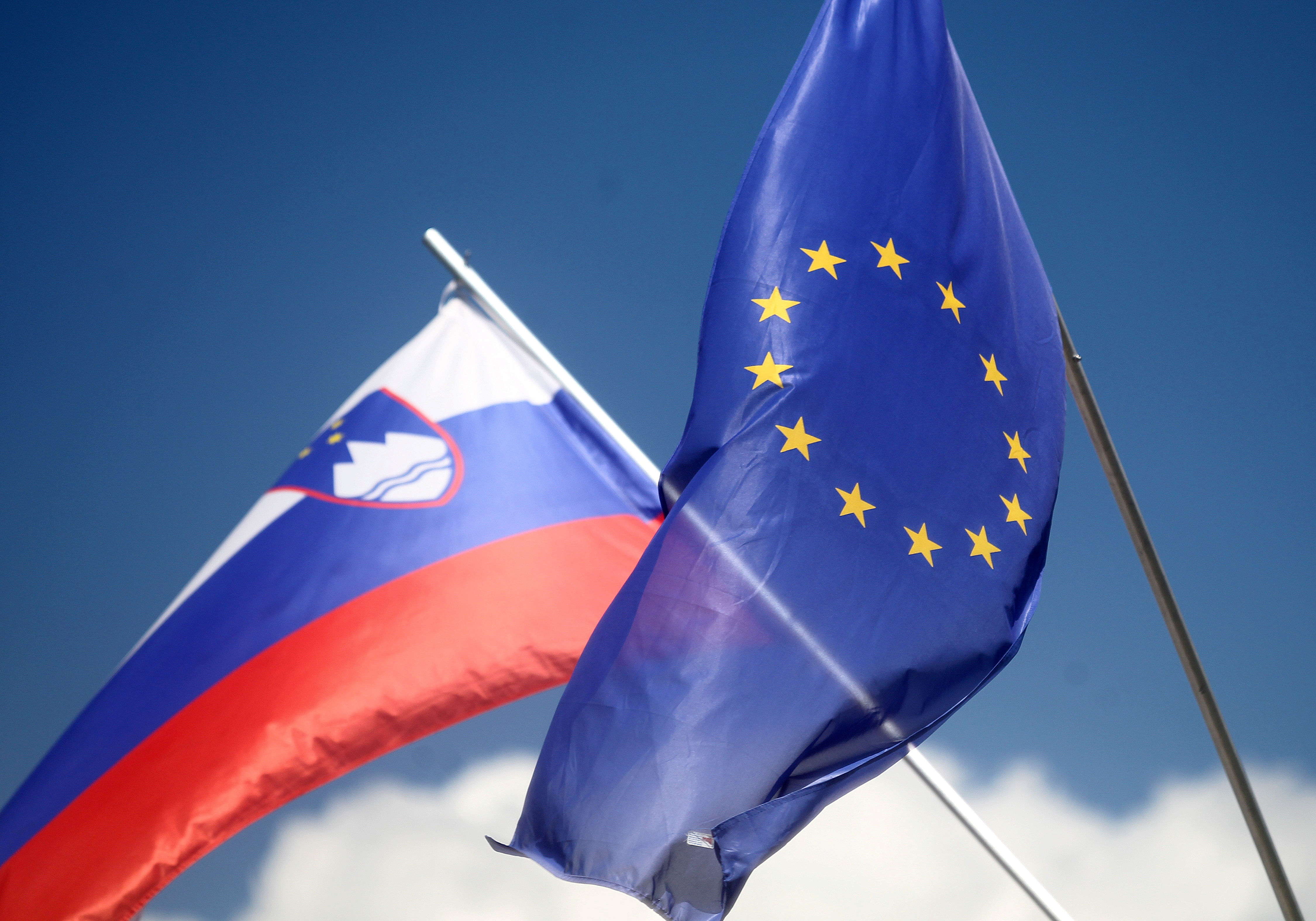The European and Slovenian flags flutter ahead of the start of Slovenia's EU presidency in Medvode, Slovenia June 30, 2021. REUTERS/Srdjan Zivulovic/File Photo