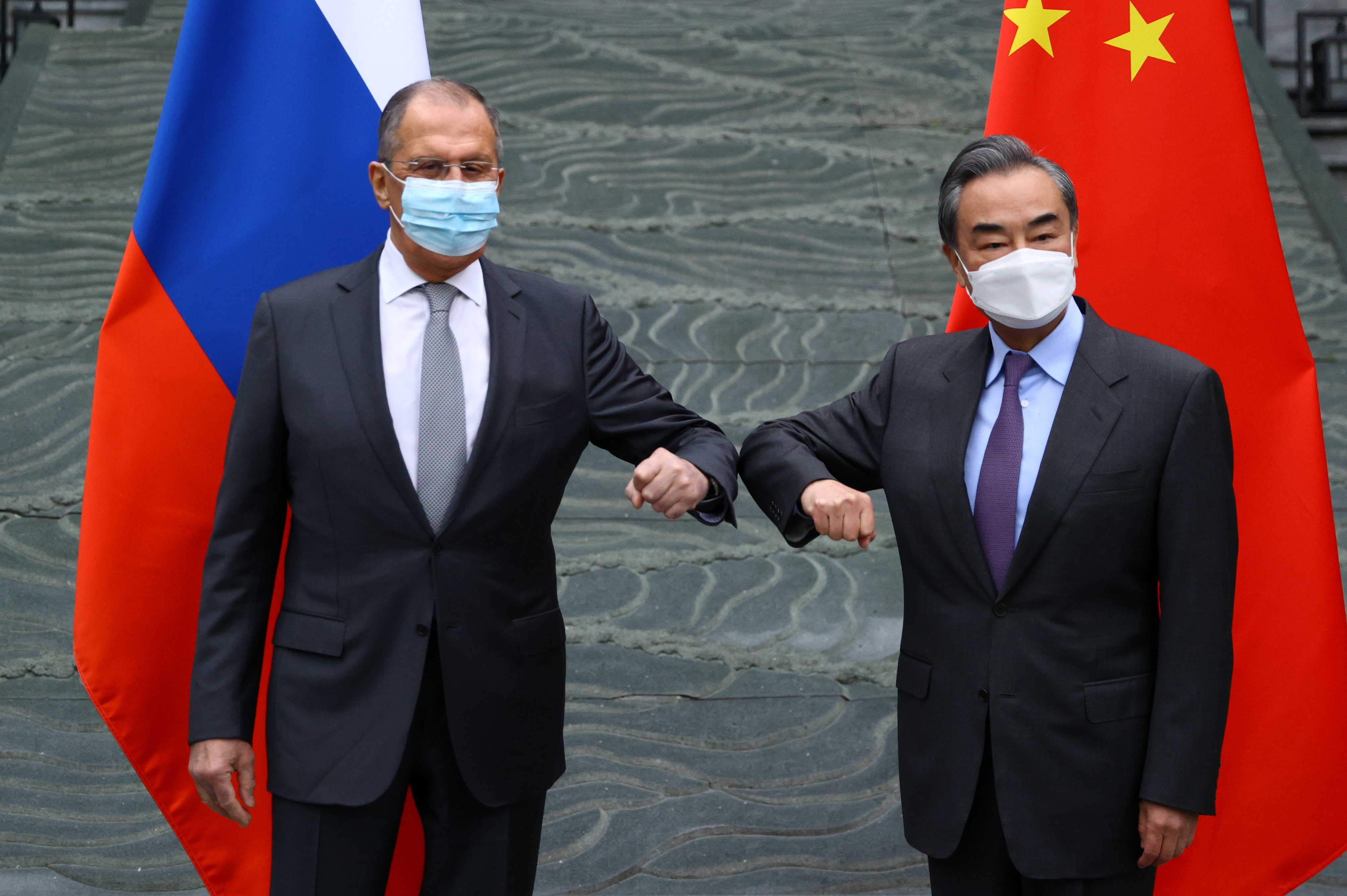 Russia's Foreign Minister Sergei Lavrov and China's State Councilor and Foreign Minister Wang Yi wearing protective face masks pose for a picture during a meeting in Guilin, China March 22, 2021. Russian Foreign Ministry/Handout via REUTERS