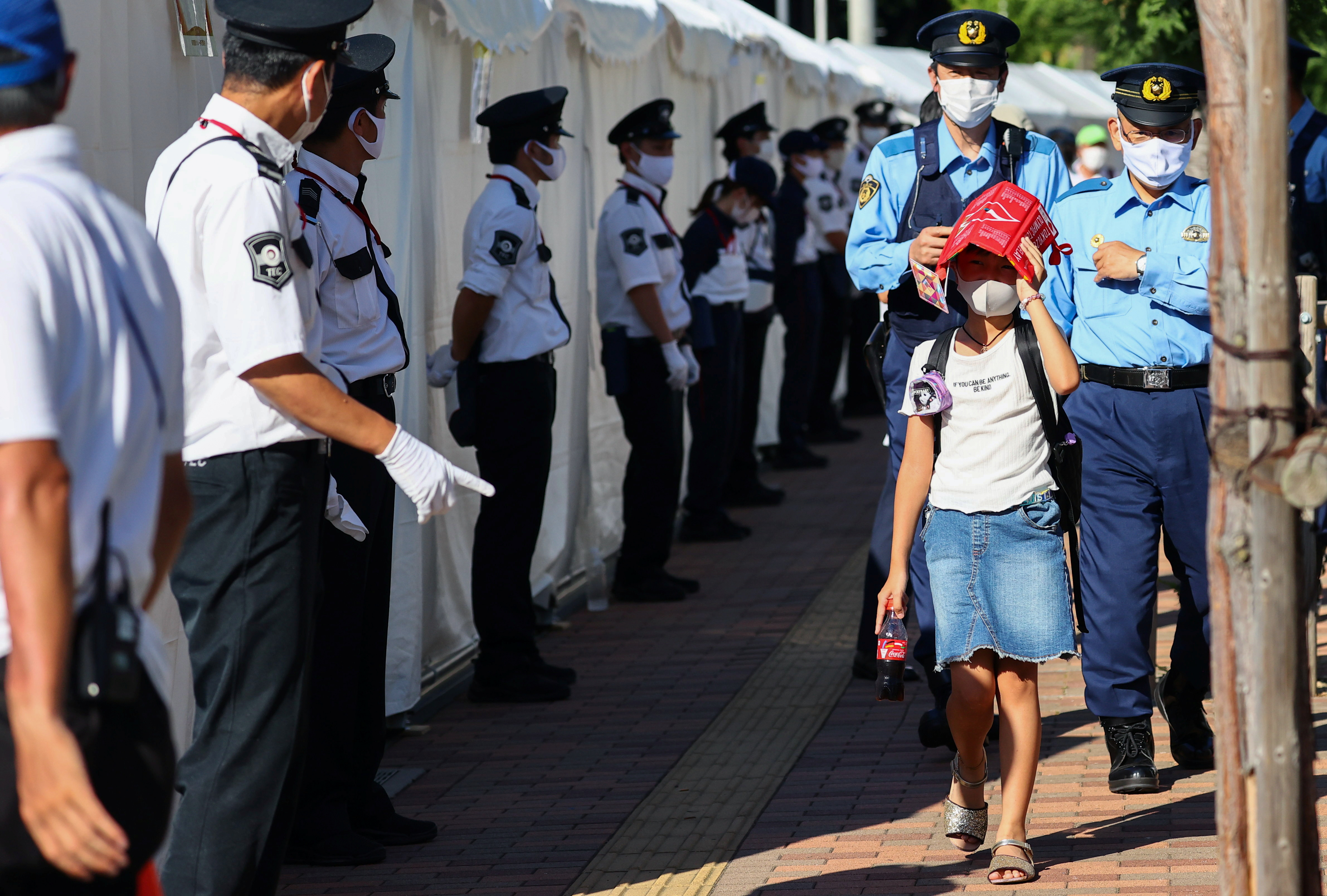 A girl covers her head to cool down as she walks next to police officers and security personnel outside a torch kiss event for the Tokyo 2020 Olympic torch relay celebration at Shinagawa Central Park in Tokyo Japan, July 21, 2021. REUTERS/Issei Kato