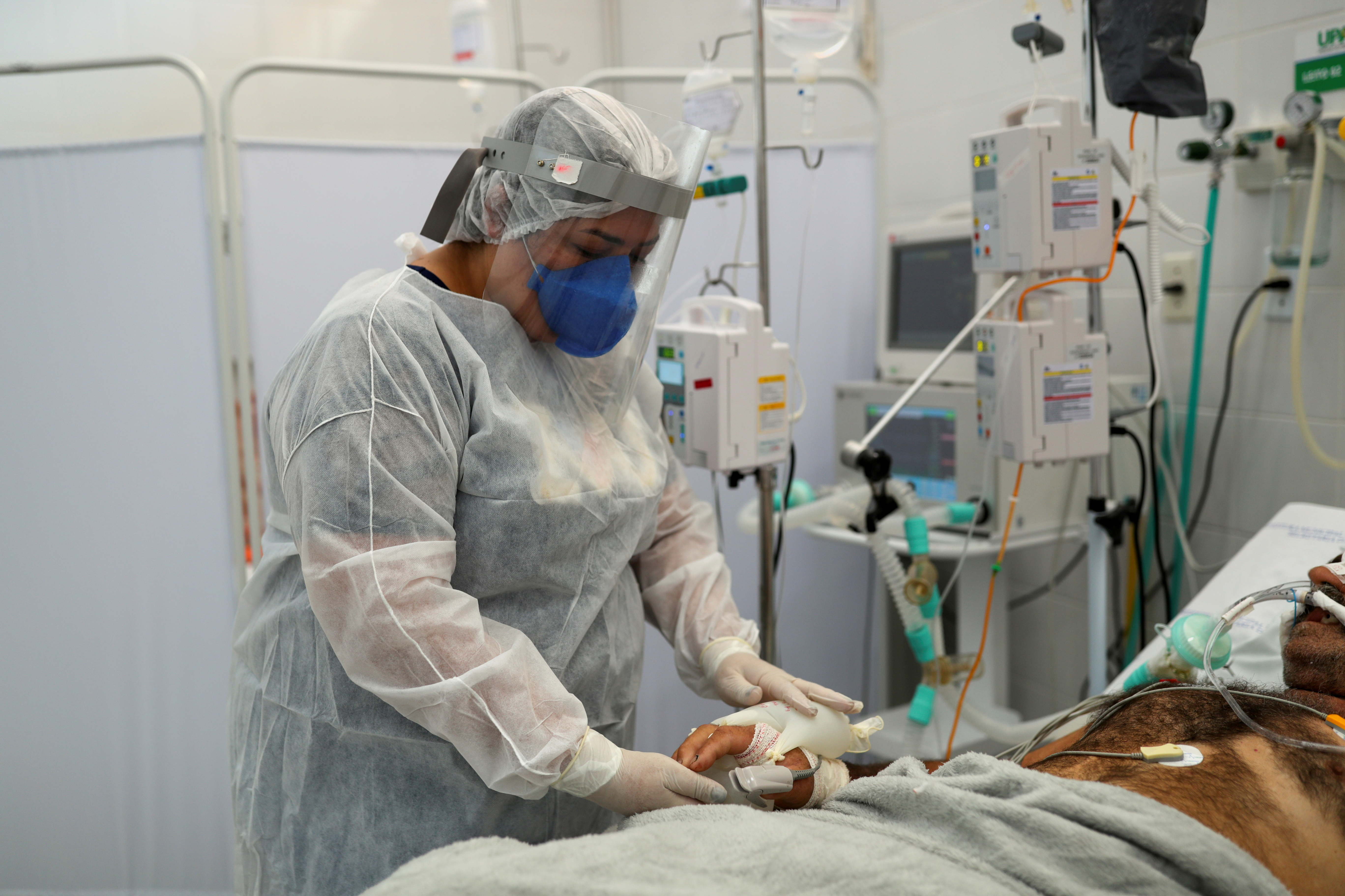 Nursing technician Semei Araujo Cunha puts what she calls 'maozinha do amor' or 'hands of love', warm water-filled gloves, on a coronavirus disease (COVID-19) patient intubated at a UPA (Emergency Service Unit) in Sao Carlos, Sao Paulo state, Brazil April 16, 2021. REUTERS/Amanda Perobelli