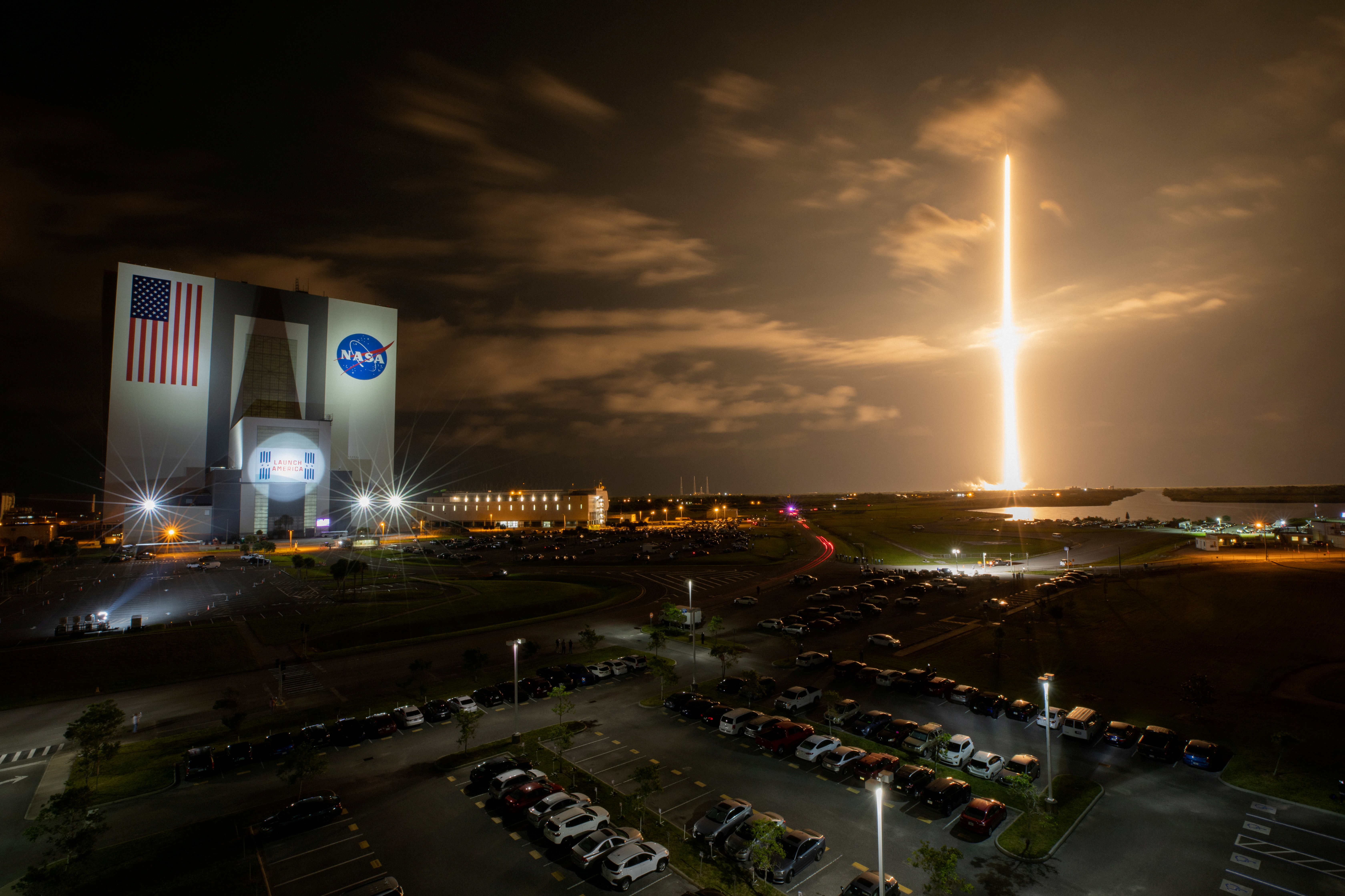With a view of the iconic Vehicle Assembly Building at left, a SpaceX Falcon 9 rocket soars upward from Launch Complex 39A carrying the company's Crew Dragon Endeavour capsule and four Crew-2 astronauts towards the International Space Station at NASA's Kennedy Space Center in Cape Canaveral, Florida, U.S. April 23, 2021.   NASA/Ben Smegelsky/Handout via REUTERS