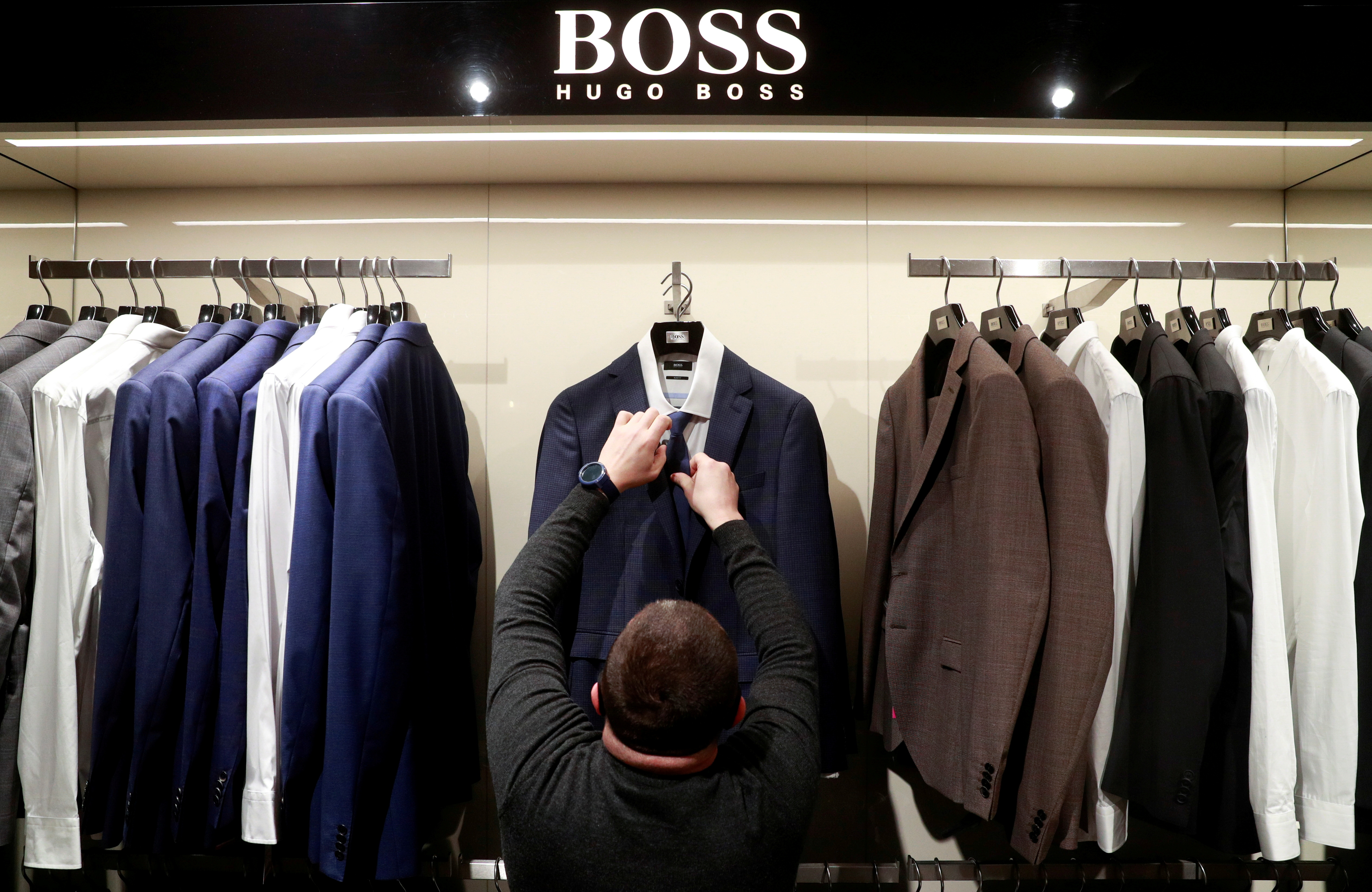 An employee displays suits at the Hugo Boss section of the Central Universal Department Store (TsUM), on the first day after ending a coronavirus lockdown, in Kyiv, Ukraine January 25, 2021. REUTERS/Valentyn Ogirenko/File Photo