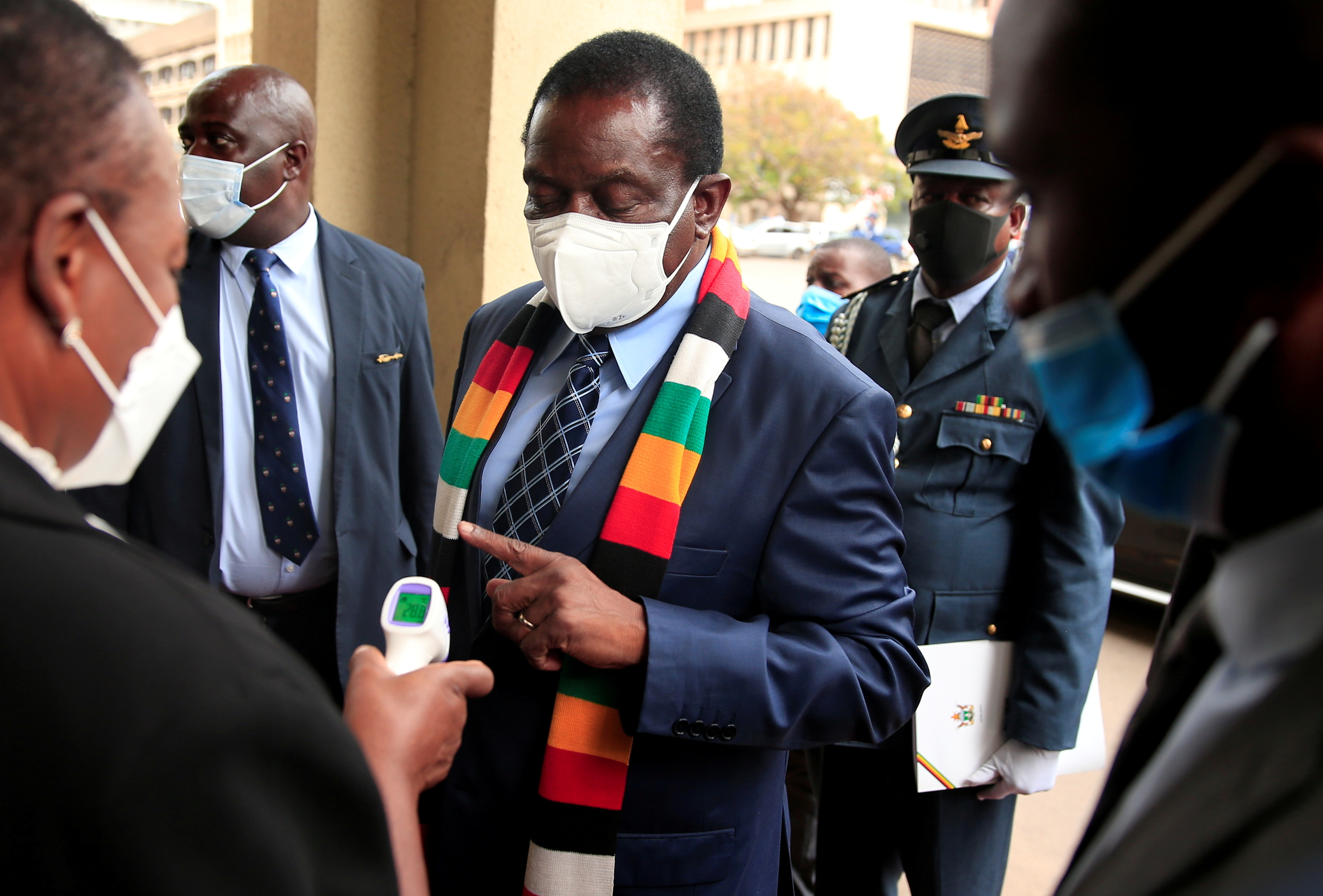 Zimbabwean President Emmerson Mnangagwa has his temperature taken as he arrives for the presentation of the 2021 National Budget at the parliament in Harare, Zimbabwe, November 26, 2020. REUTERS/Philimon Bulawayo/File Photo