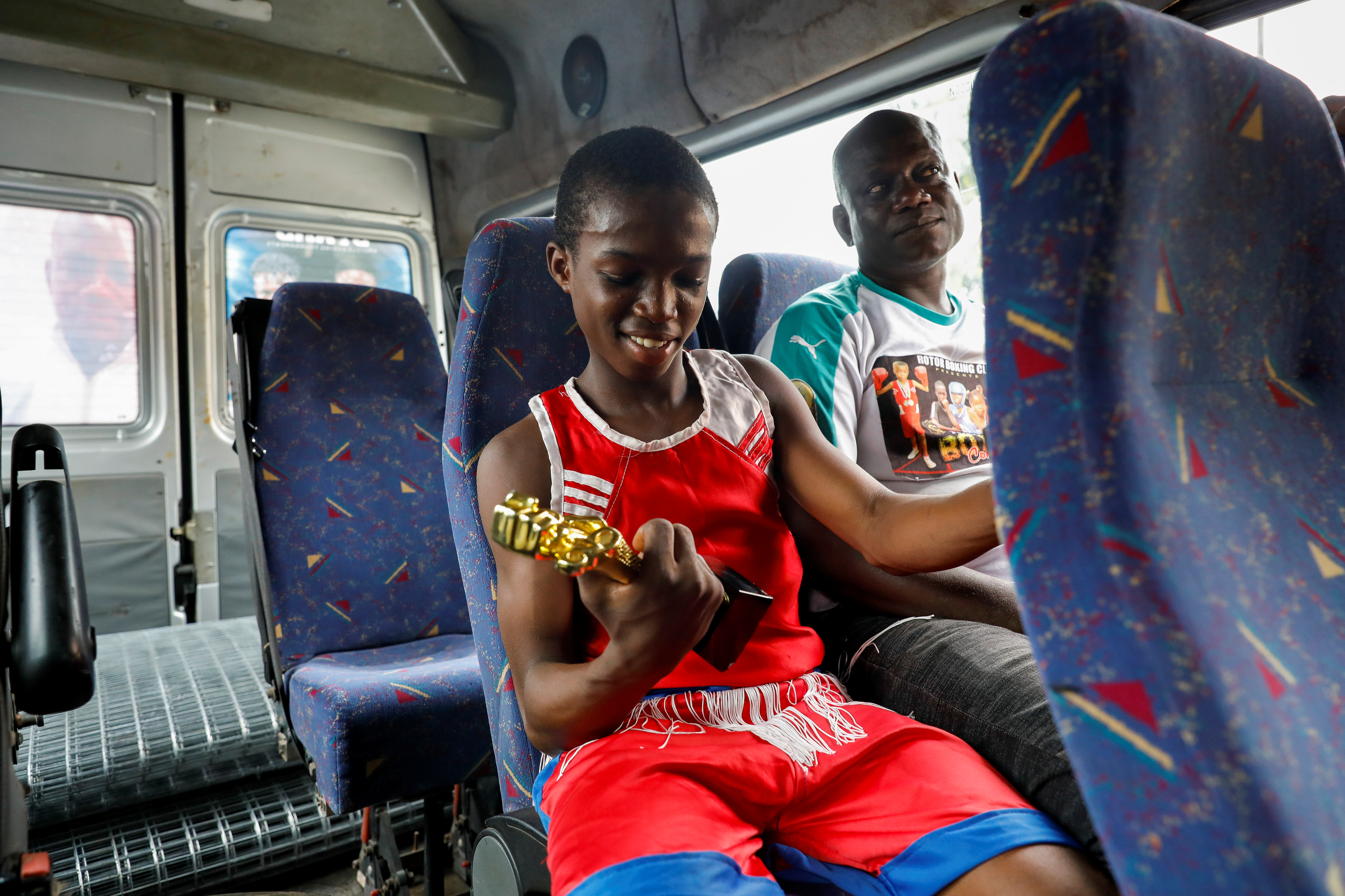 Boxer Tijani Abdulazeez, popularly known as TJ, 15, looks at his trophy on his way home after winning the youth tournament in Iyana-ipaja, Lagos, Nigeria June 26, 2021.  REUTERS/Temilade Adelaja