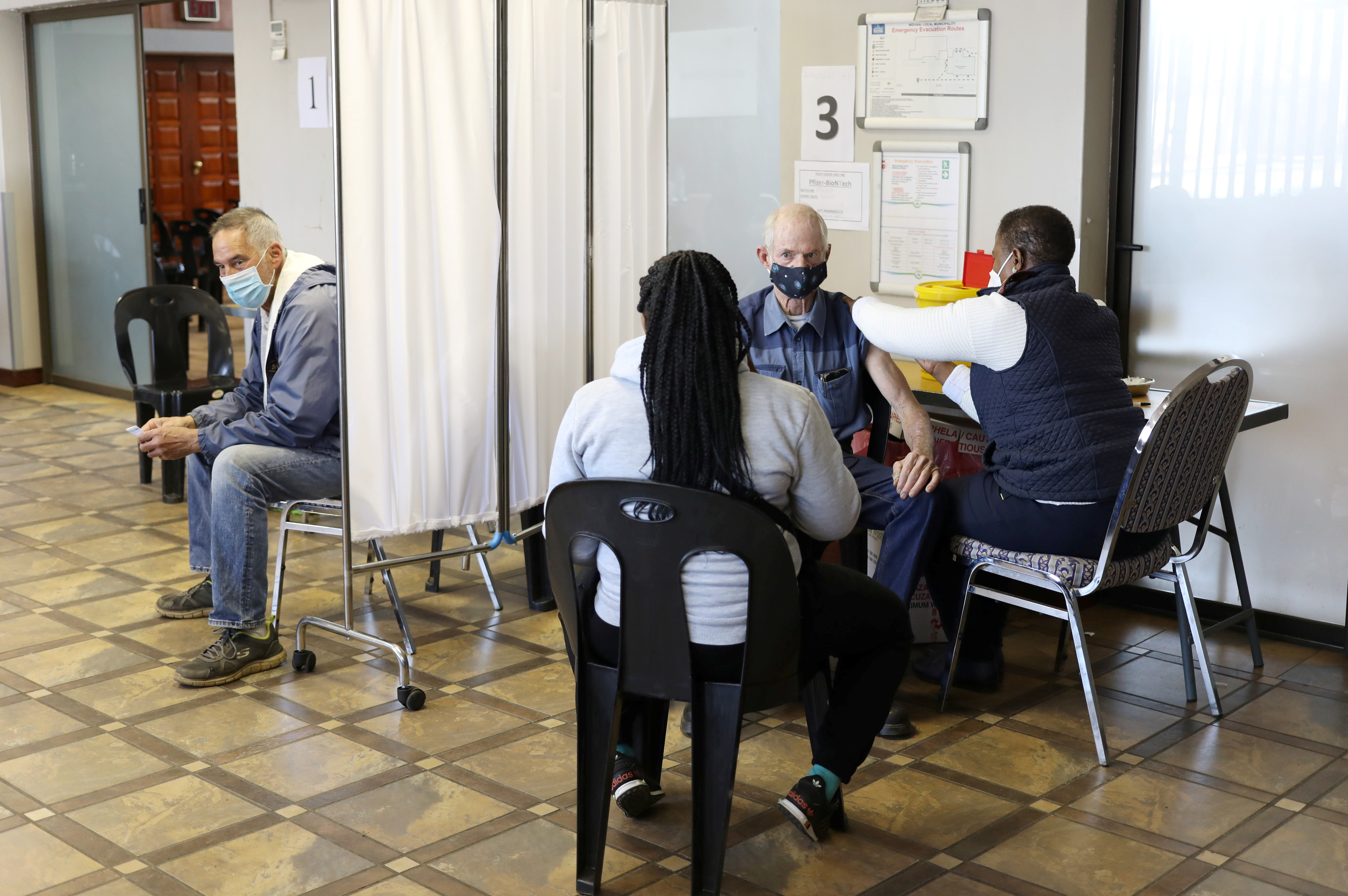 A man is vaccinated as another looks on while waiting to receive a dose of a coronavirus disease (COVID-19) vaccine in Meyerton, south of Johannesburg, South Africa June 23, 2021. REUTERS/Siphiwe Sibeko