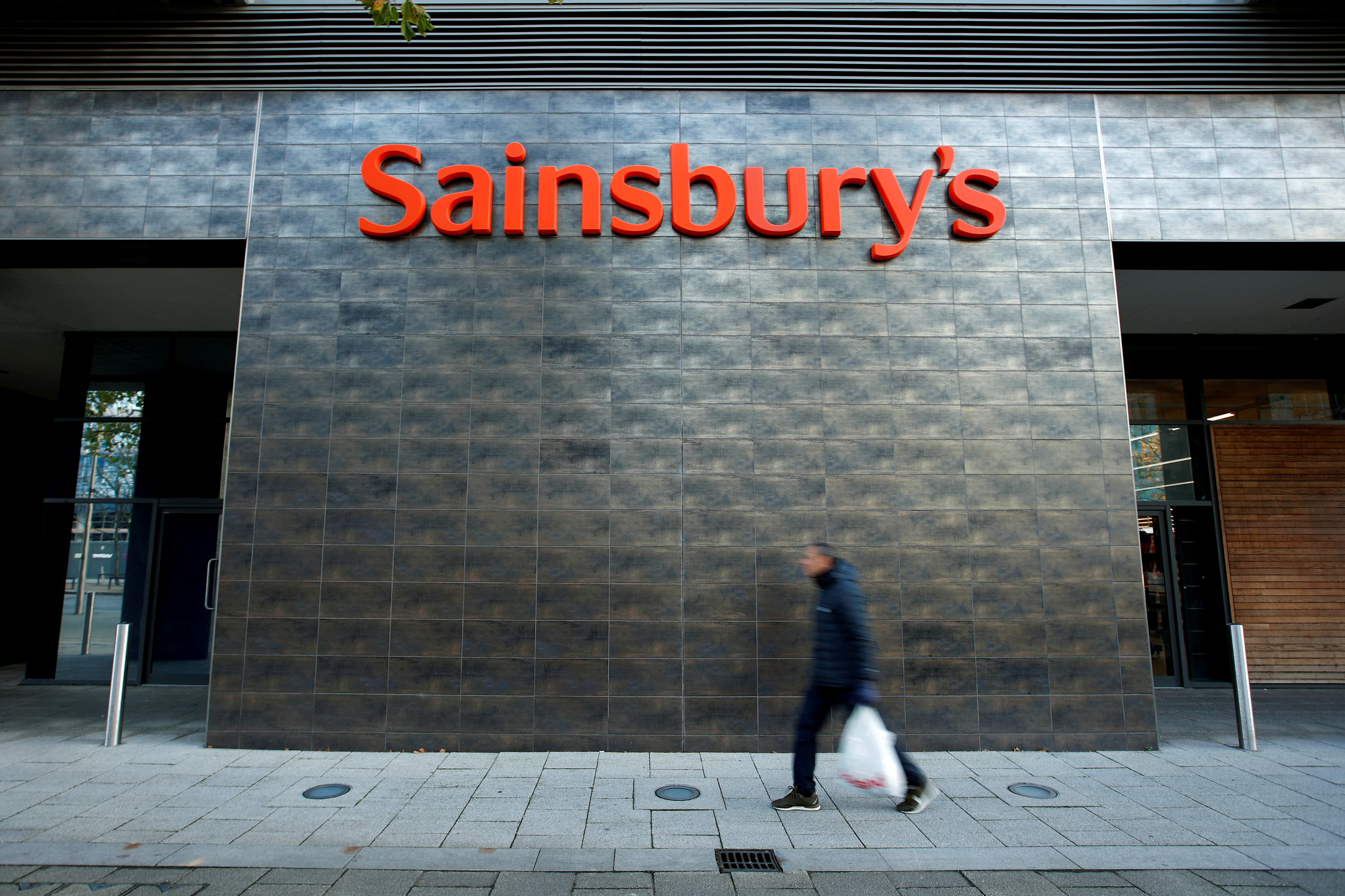 A person walks past a Sainsbury's store in Milton Keynes, Britain November 5, 2020. REUTERS/Andrew Boyers/File Photo