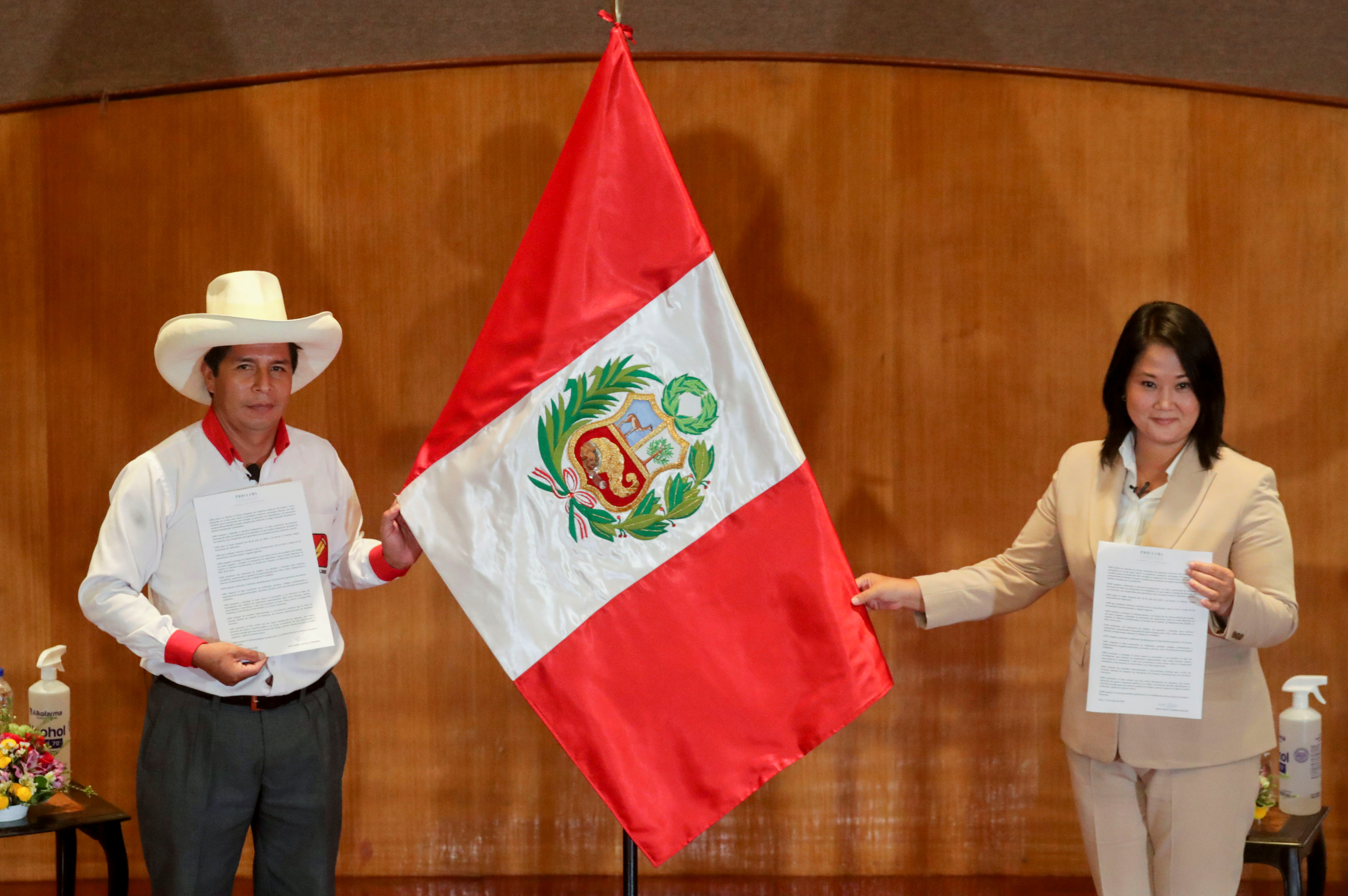 Peruvian presidential candidates Pedro Castillo and Keiko Fujimori, who will face each other in a run-off vote on June 6, hold Peru's national flag after signing a