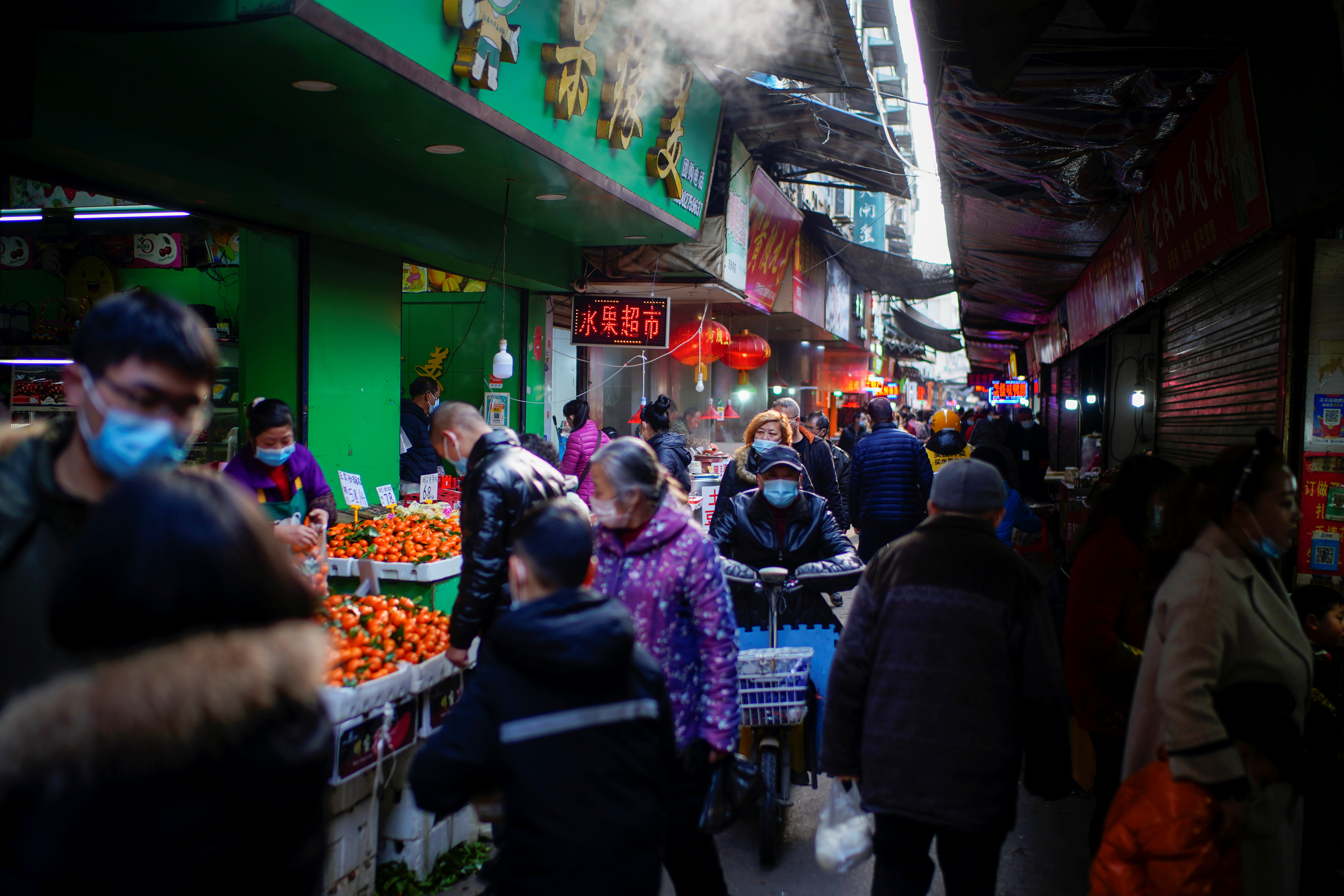People wearing face masks walk on a street market, following an outbreak of the coronavirus disease (COVID-19) in Wuhan, Hubei province, China February 8, 2021. REUTERS/Aly Song
