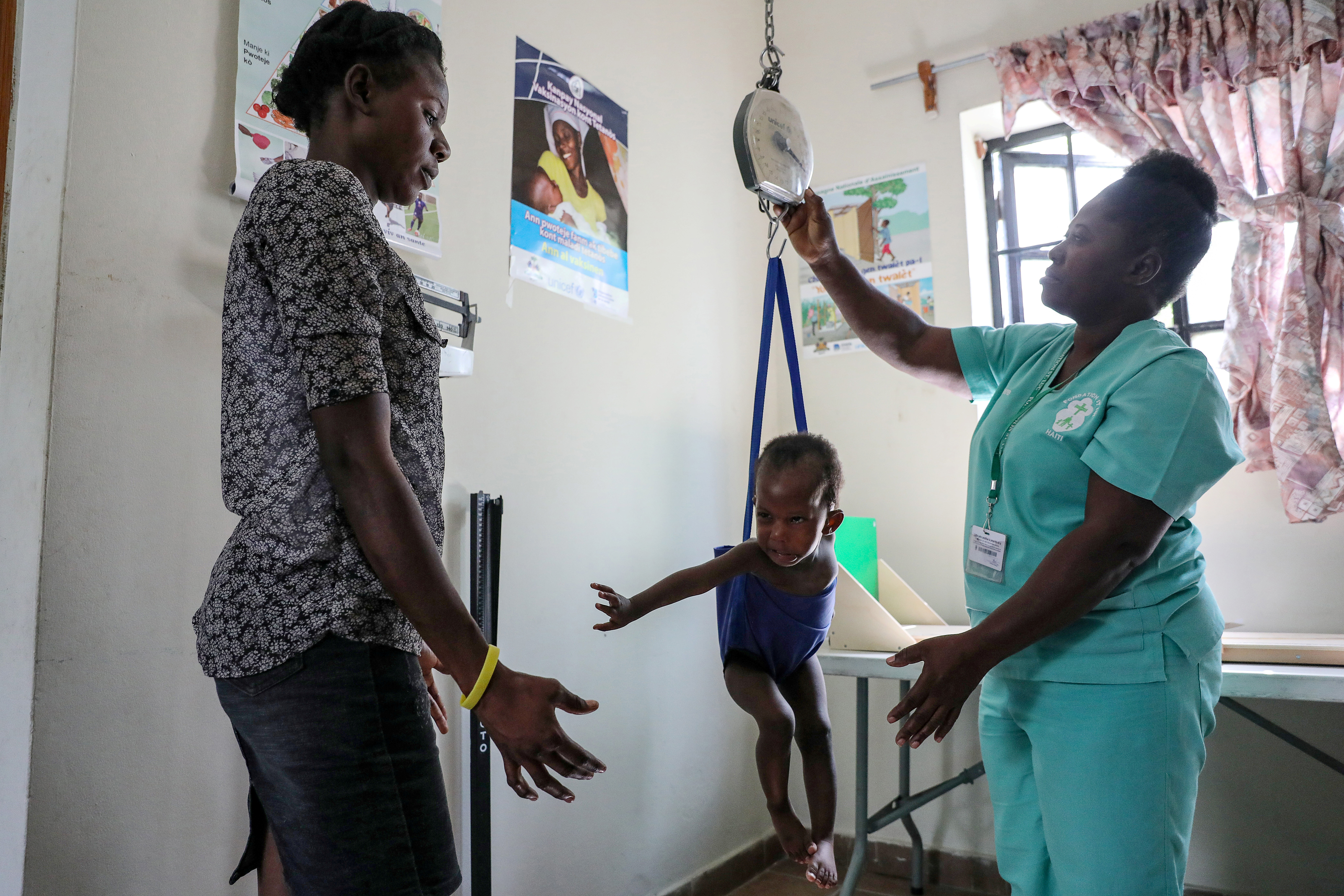 A nurse weighs a child in front of its mother at St. Luke Hospital in Port-au-Prince, Haiti January 29, 2020. Picture taken January 29, 2020. REUTERS/Valerie Baeriswyl/File Photo