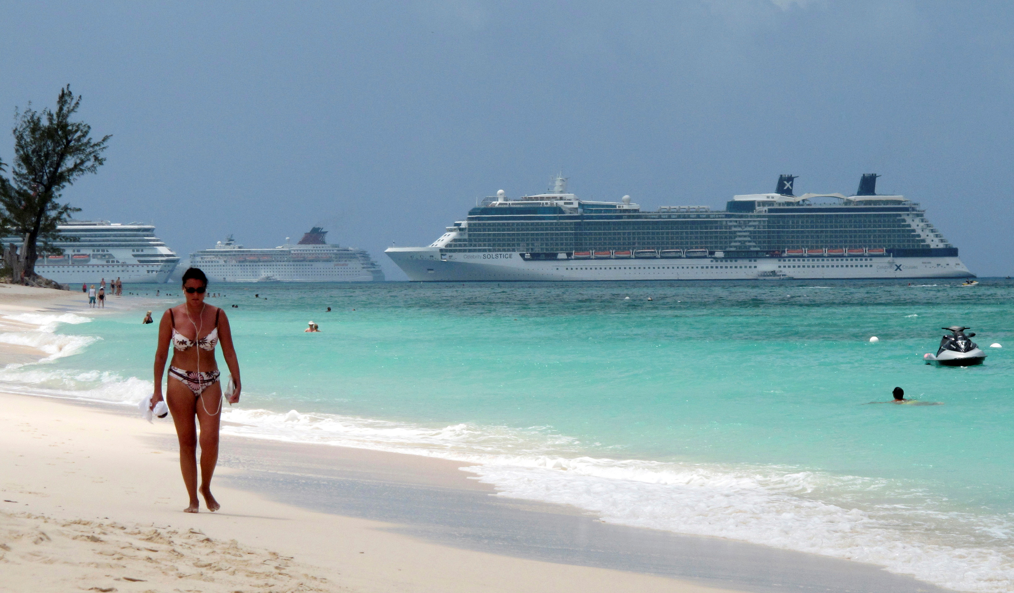 A woman walks along Seven Mile Beach with three cruise ships anchored in port in George Town, Cayman Islands, April 27, 2010. REUTERS/Gary Hershorn