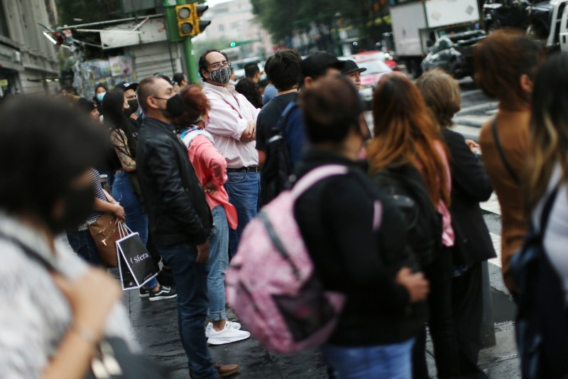 People wearing face masks wait at a traffic junction as Mexico City's authorities announce a full reopening of the city come Monday, the first time since the coronavirus disease (COVID-19) pandemic, Mexico June 4, 2021. REUTERS/Edgard Garrido