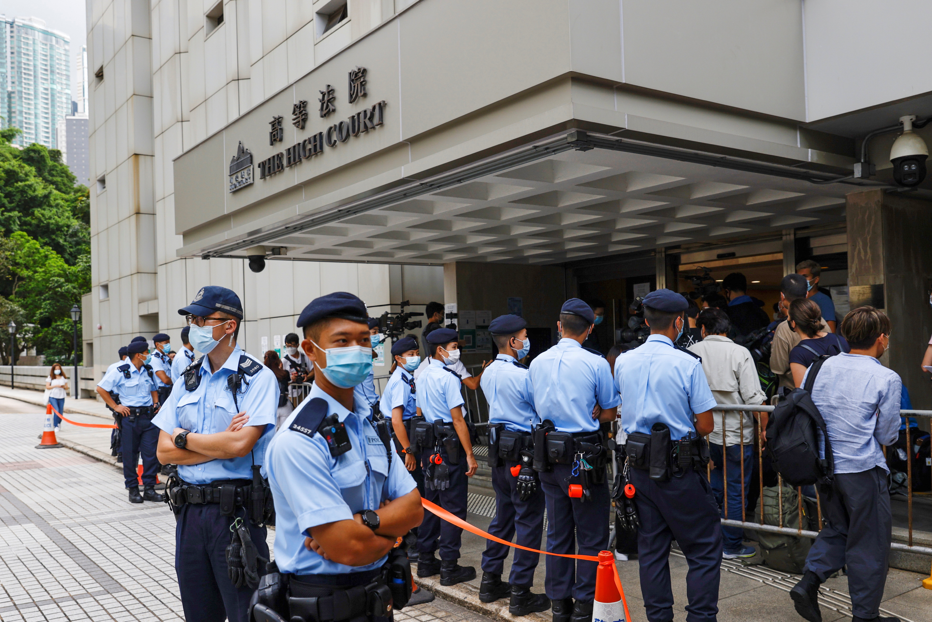 Police stand guard outside the High Court during court hearing of Tong Ying-kit, the first person charged under a new national security law, in Hong Kong, China. July 30, 2021. REUTERS/Tyrone Siu