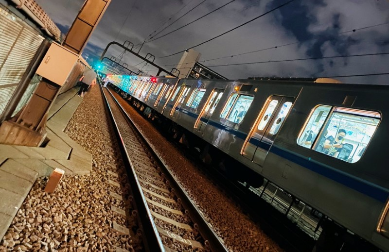 People walk along railway tracks after a knife attack on a train in Tokyo, Japan August 6, 2021 in this picture obtained from social media. TWITTER/_KING_OF_SKY/via REUTERS