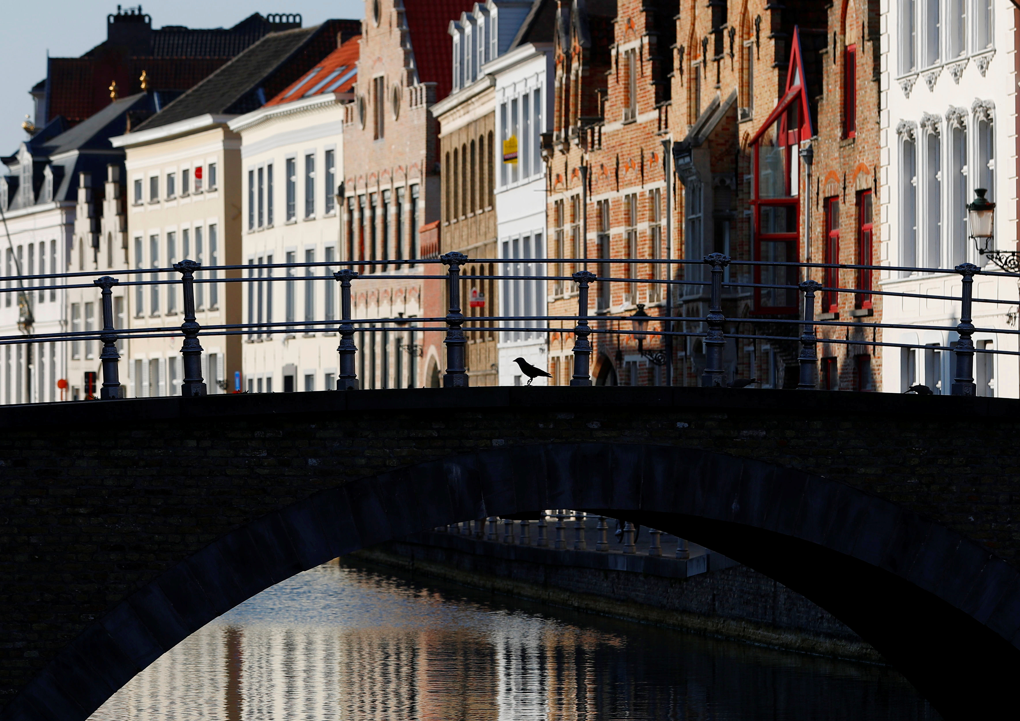 A pigeon is seen on a deserted bridge crossing a canal in the old town of Bruges during the lockdown imposed by the Belgian government, Belgium April 21, 2020. REUTERS/Francois Lenoir