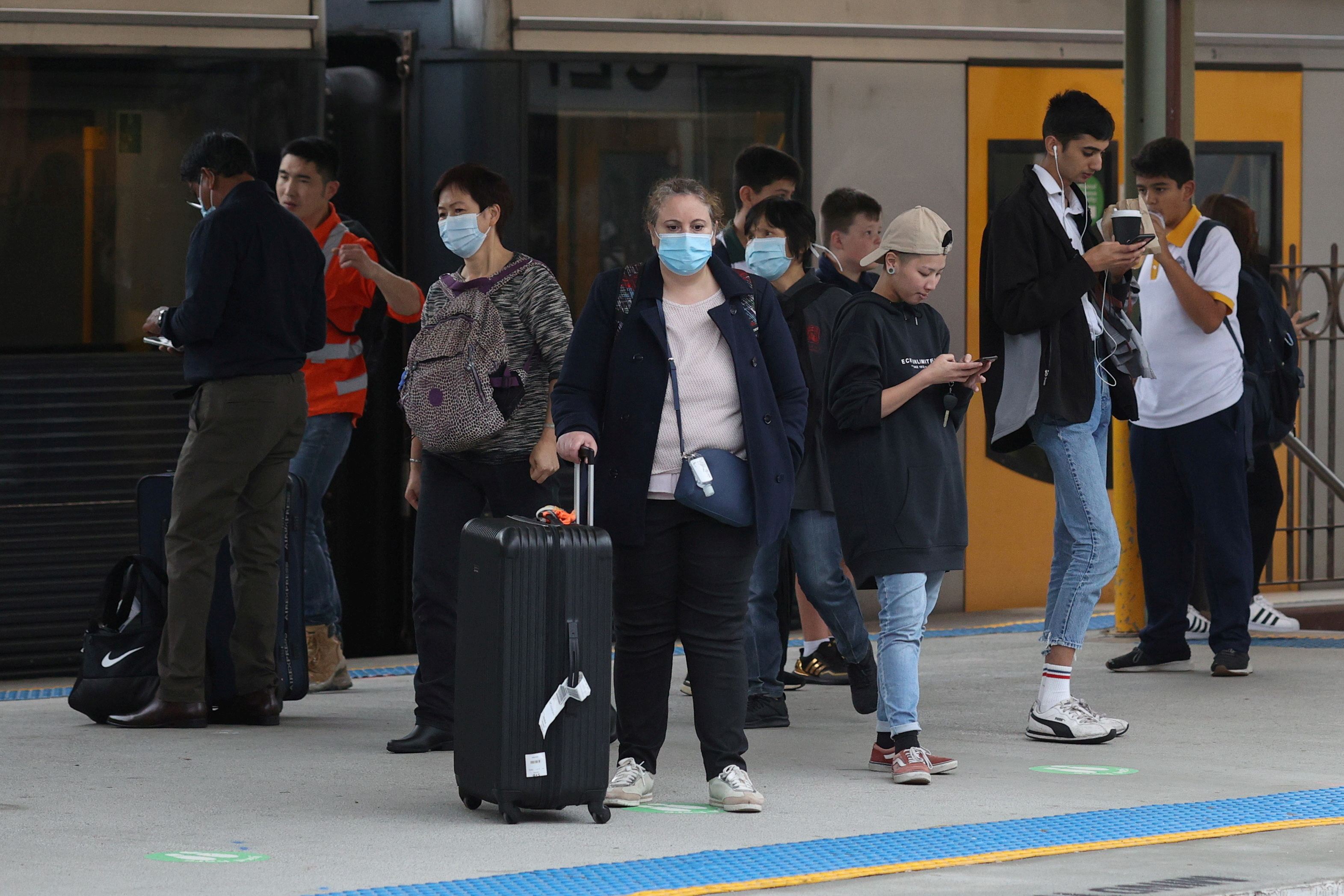 People, some wearing protective face masks, stand on a train platform at Central Station after new public health regulations were announced for greater Sydney, including compulsory mask-wearing on public transport, following the emergence of new cases of the coronavirus disease (COVID-19) in Sydney, Australia, May 6, 2021.  REUTERS/Loren Elliott