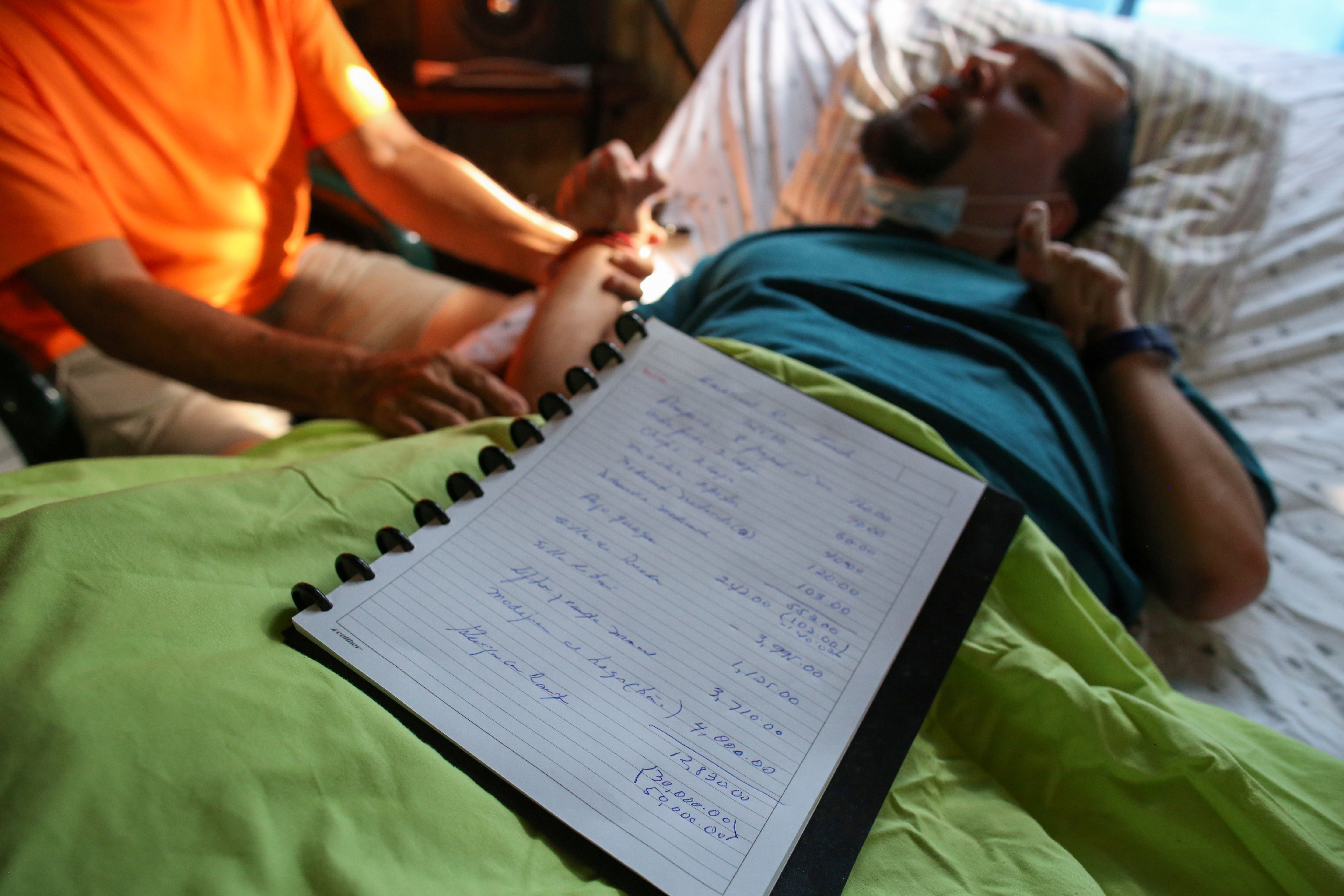 A handwritten list made by Abraham Rivera Berrios shows the details of the expenses involved in caring for his son Emanuel Rivera, who was born severely disabled and needs constant care, at his home, in Toa Alta, Puerto Rico, September 22, 2021. Picture taken September 22, 2021.  REUTERS/Alvin Baez