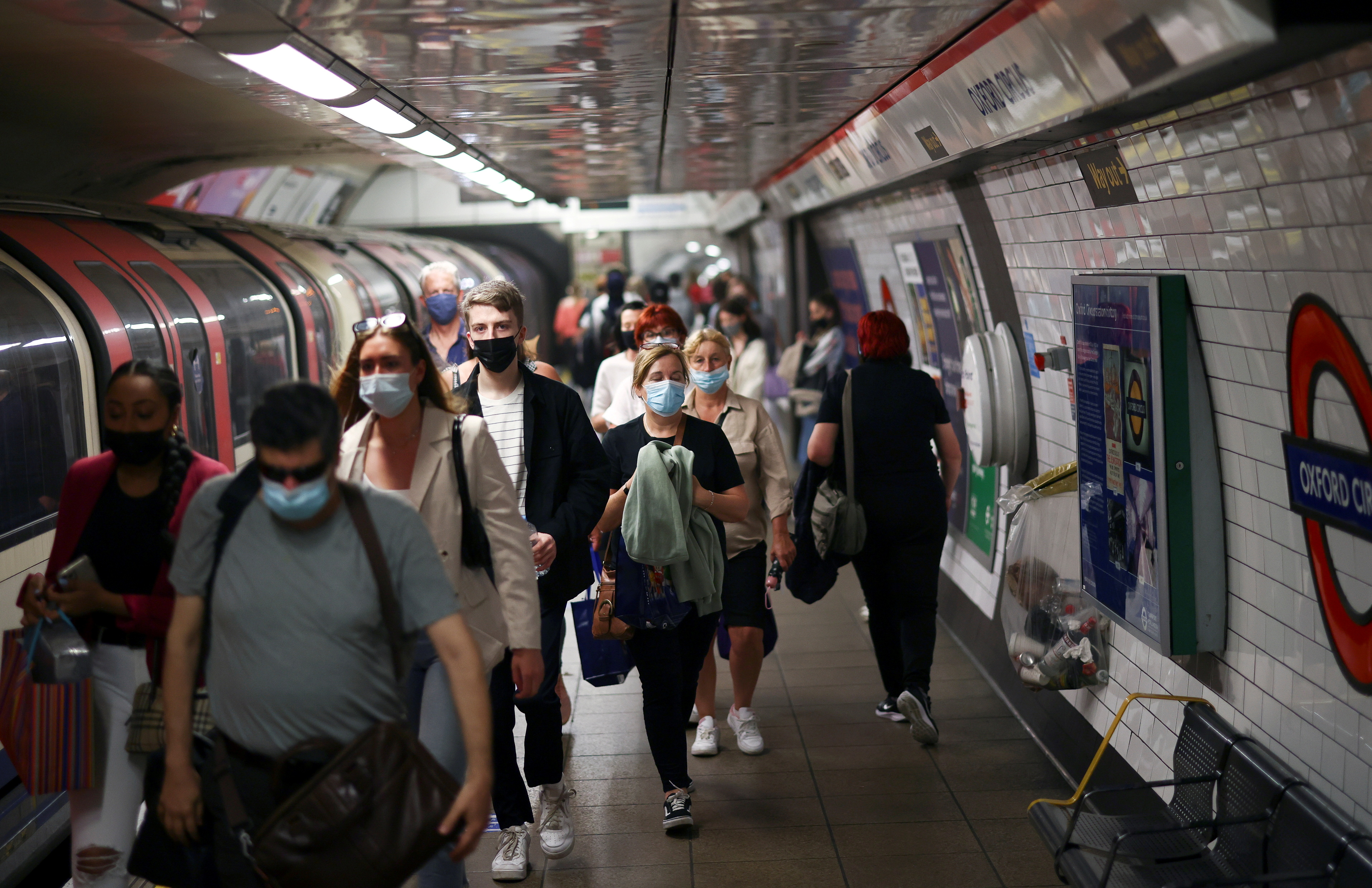 People, some wearing protective face masks, walk along a platform at Oxford Circus underground station, amid the coronavirus disease (COVID-19) pandemic, in London, Britain, July 4, 2021. REUTERS/Henry Nicholls