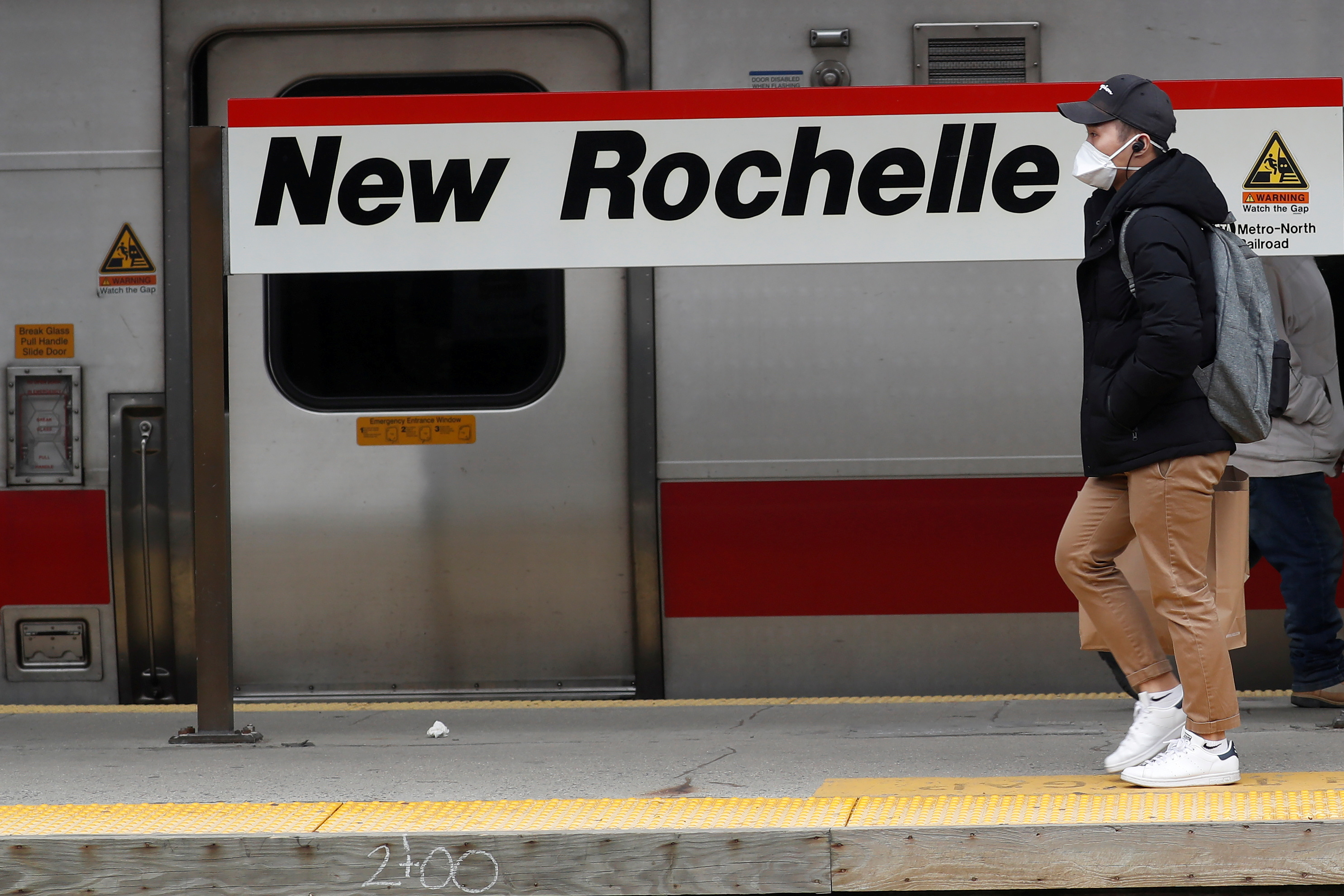 A man wears a mask as he walks on a commuter train platform during the coronavirus outbreak in New Rochelle, New York, U.S., March 12, 2020. REUTERS/Shannon Stapleton/File Photo