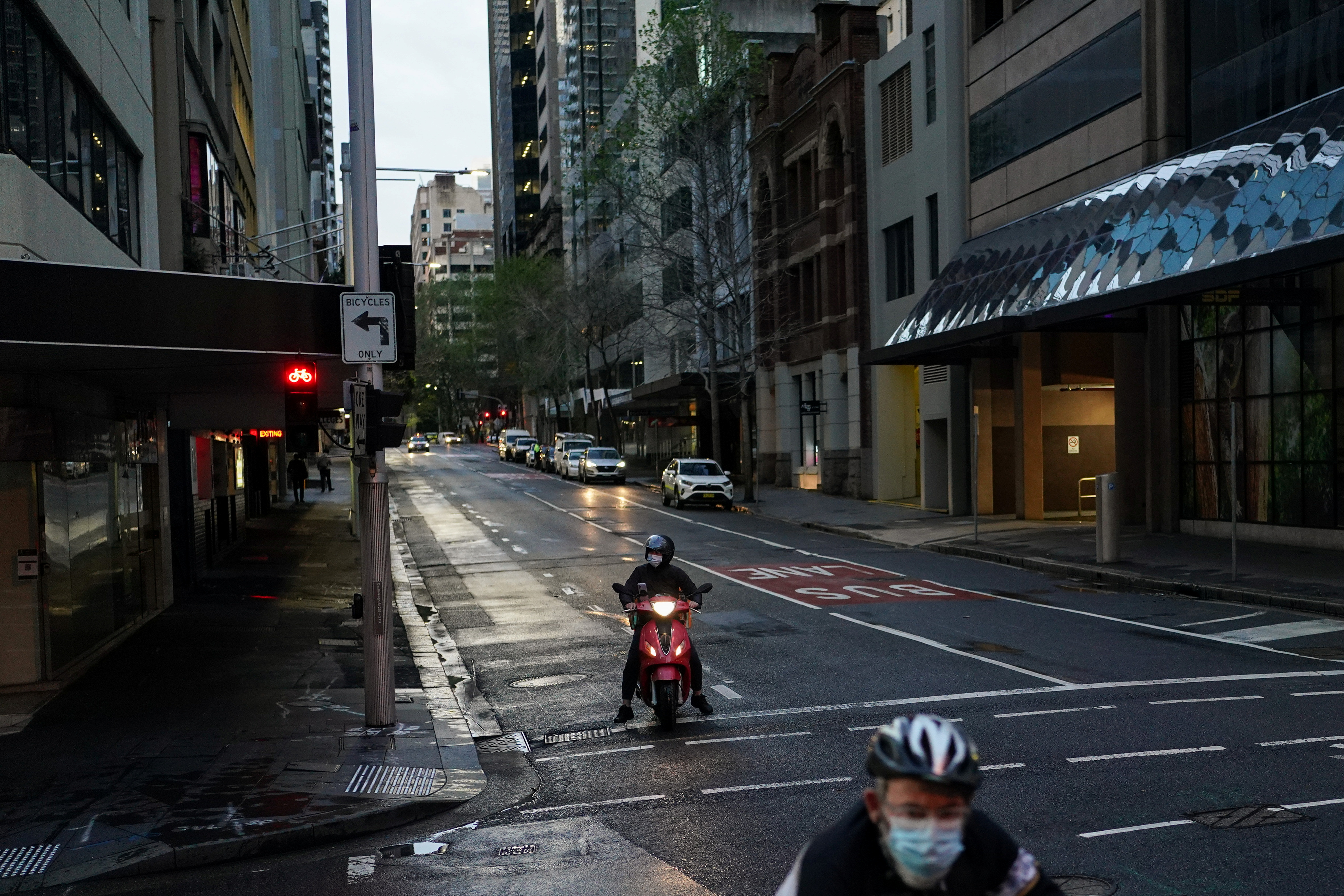 A delivery courier on motorbike and a cyclist, both wear protective face masks, navigates the city centre during a lockdown to curb the spread of a coronavirus disease (COVID-19) outbreak in Sydney, Australia, September 14, 2021.  REUTERS/Loren Elliott