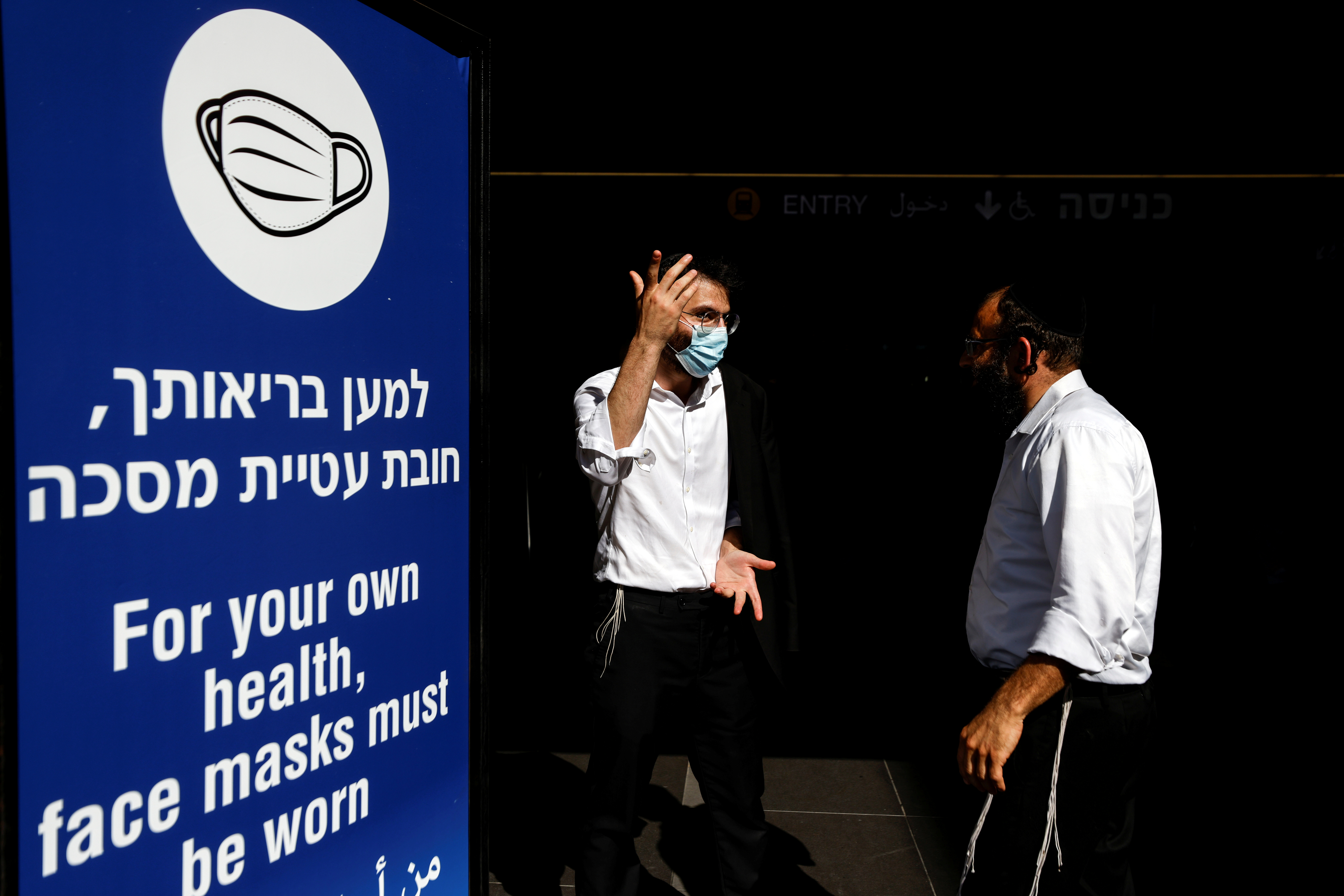 Men stand next to an information banner at Israel's Ben Gurion International Airport, amid a spread of the Delta variant of the coronavirus disease (COVID-19), near Tel Aviv, Israel July 8, 2021. REUTERS/Amir Cohen/File Photo