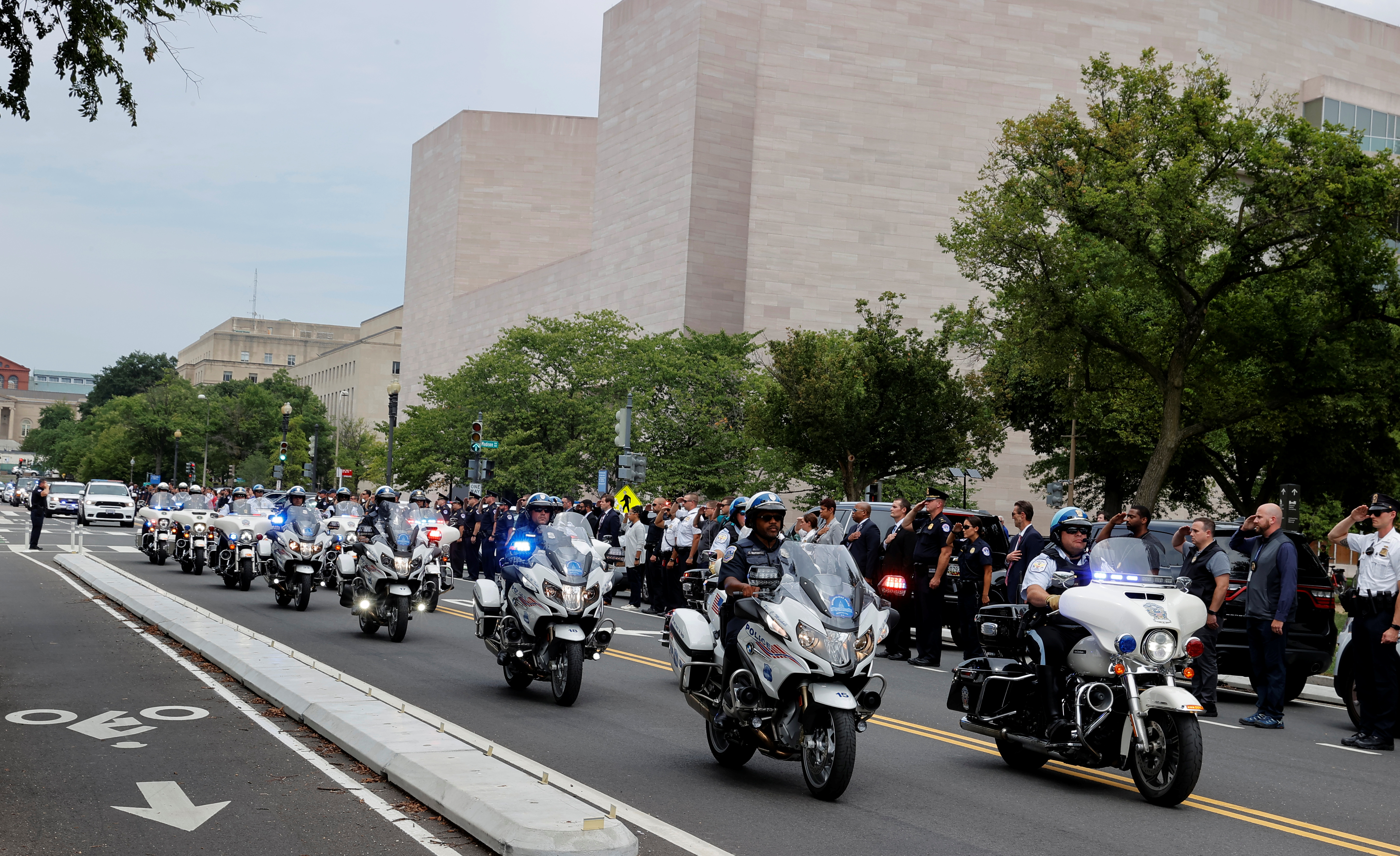Law enforcement officers from Washington's Metropolitan Police Department, the U.S. Capitol Police, the Pentagon Force Protection Agency and other police departments ride in a ceremonial procession past the East Wing of the National Gallery of Art as other officers salute a police officer wounded in a shooting outside the Pentagon earlier in the day in Washington, August 3, 2021.  REUTERS/Jim Bourg