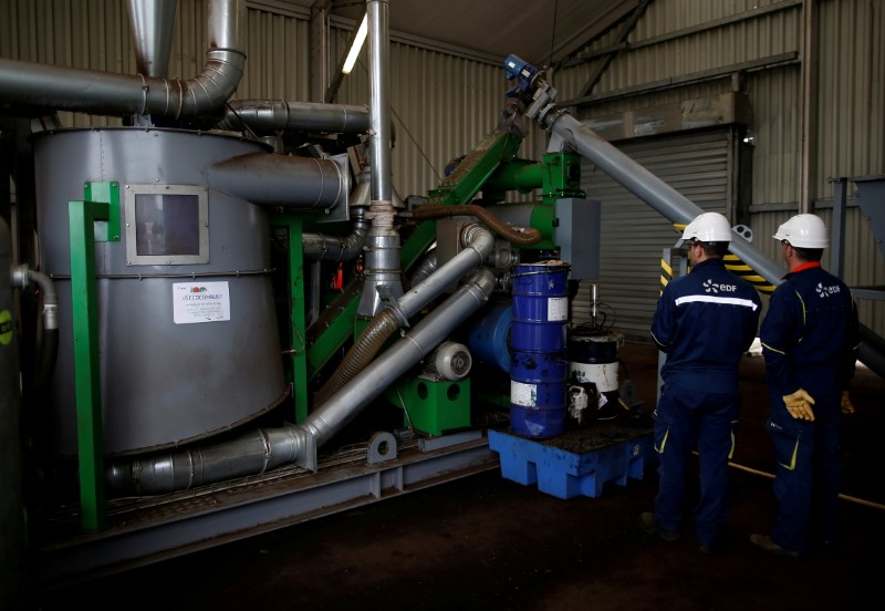 Employees of the Electricite de France (EDF) work on a prototype manufacturing densified biomass pellets at the Electricite de France (EDF) coal-fired power plant in Cordemais, near Nantes, France, March 21, 2019. REUTERS/Stephane Mahe