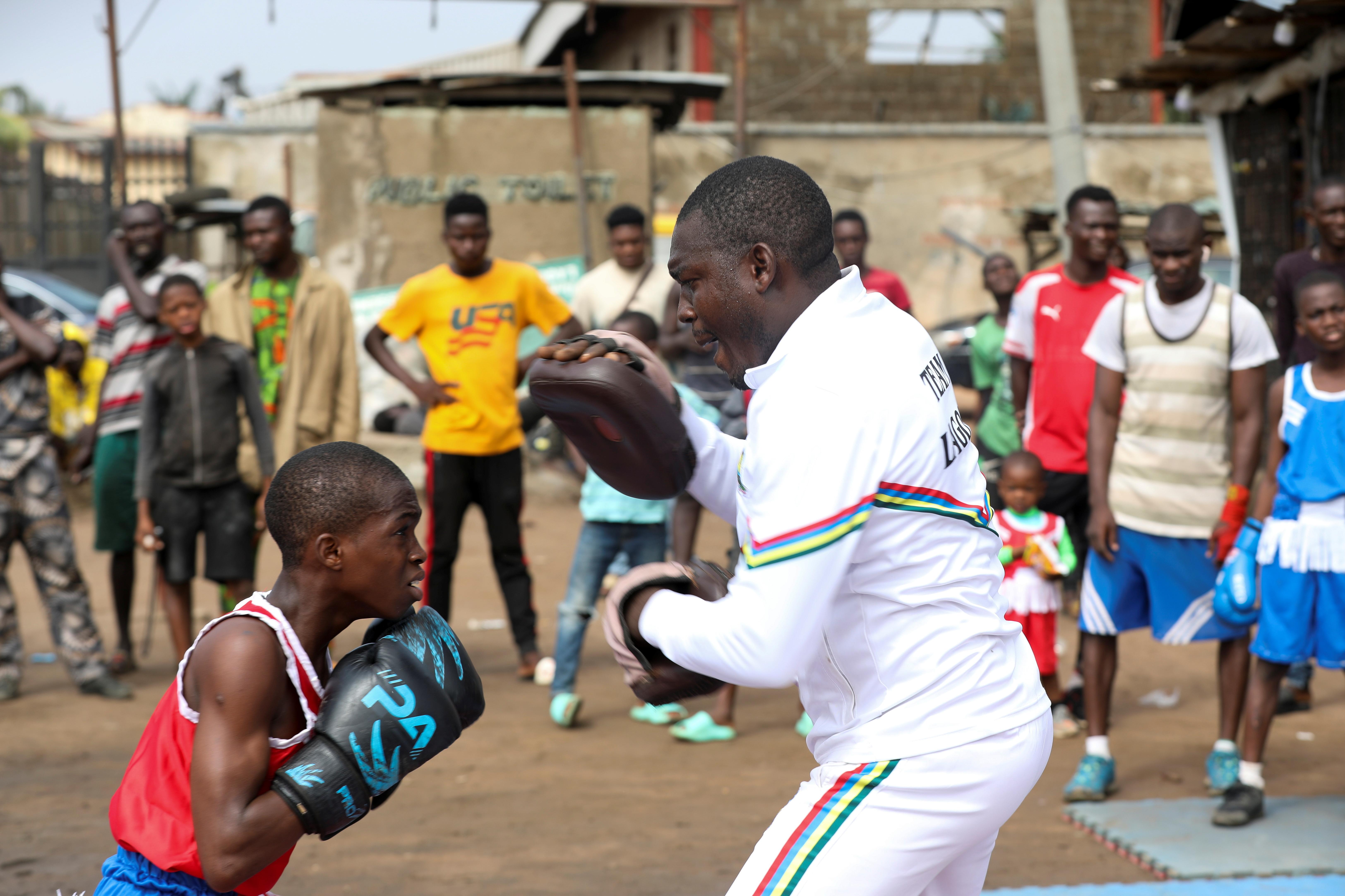 Boxer Tijani Abdulazeez, popularly known as TJ, 15, trains with his father, Abdulfathi Abdulazeez, at an outdoor boxing gym in Adura playground, in Lagos, Nigeria June 5, 2021. REUTERS/Temilade Adelaja