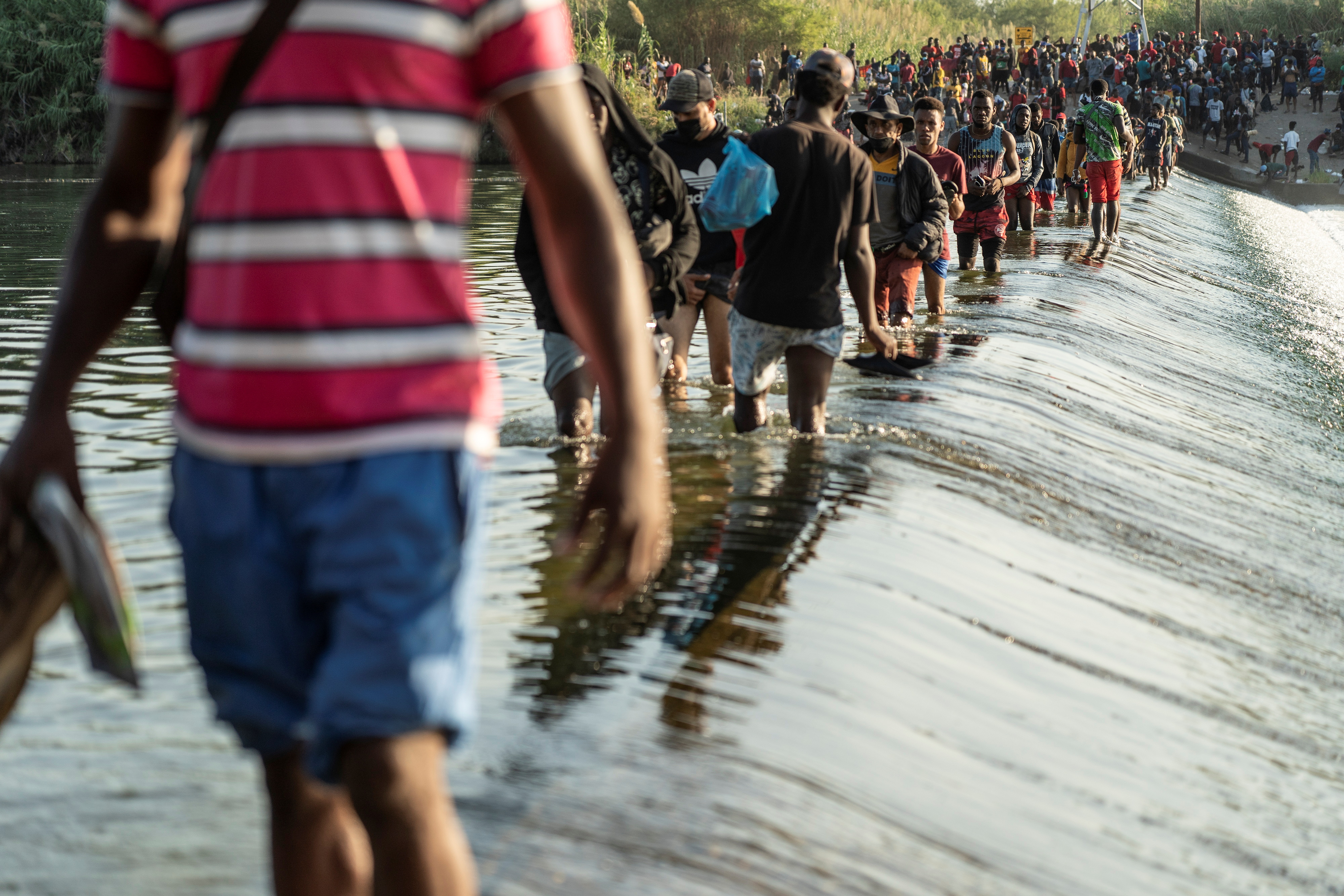 Migrants seeking asylum in the U.S. walk in the Rio Grande river near the International Bridge between Mexico and the U.S., as they wait to be processed, in Ciudad Acuna, Mexico, September 16, 2021. According to officials, some migrants cross back and forth into Mexico to buy food and supplies. REUTERS/Go Nakamura
