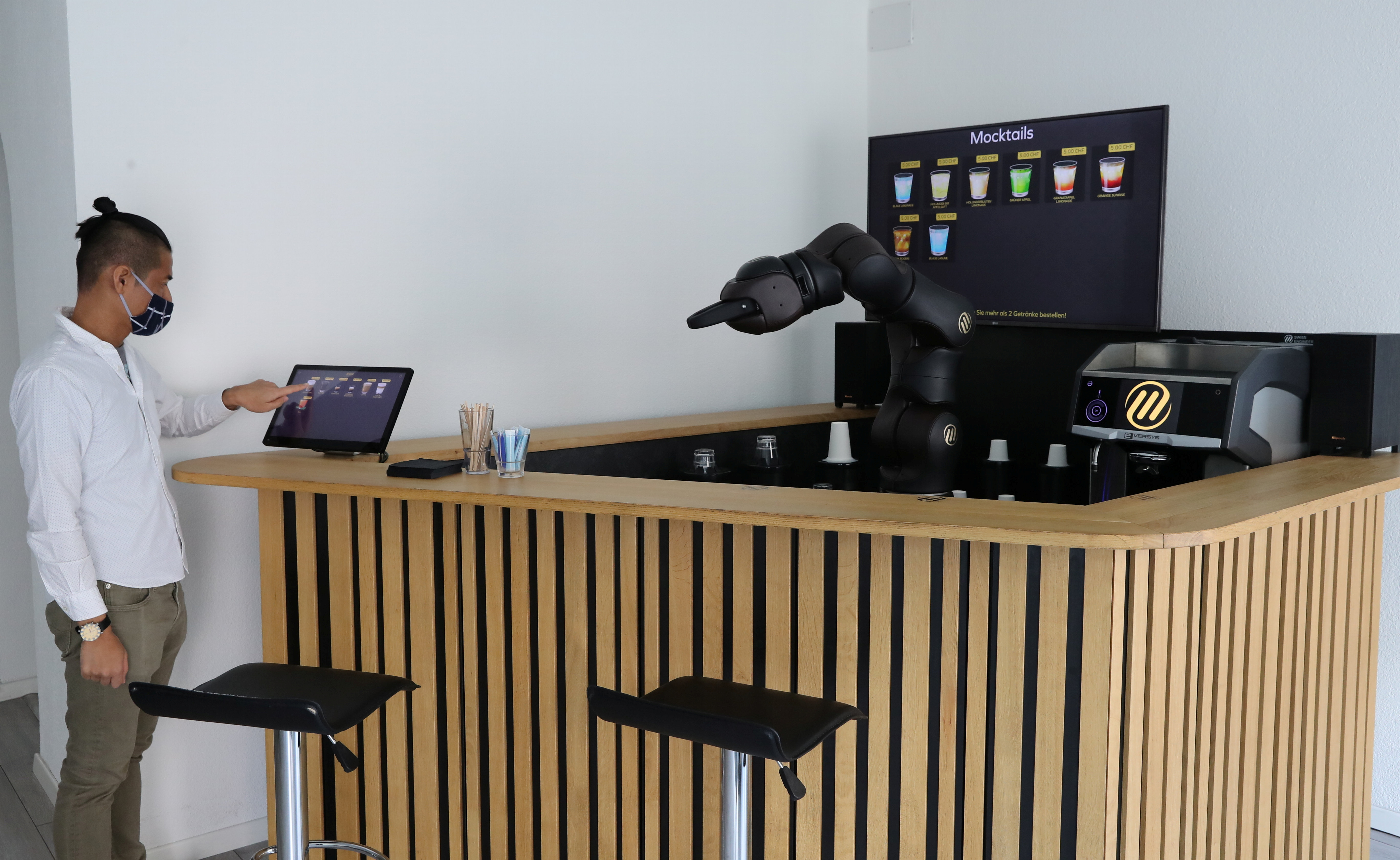 An employee taps a display to order a coffee at the Barney Barista Bar of the Swiss F&P Robotics company in Zurich, Switzerland, April 16, 2021. Picture taken April 16, 2021. REUTERS/Arnd Wiegmann